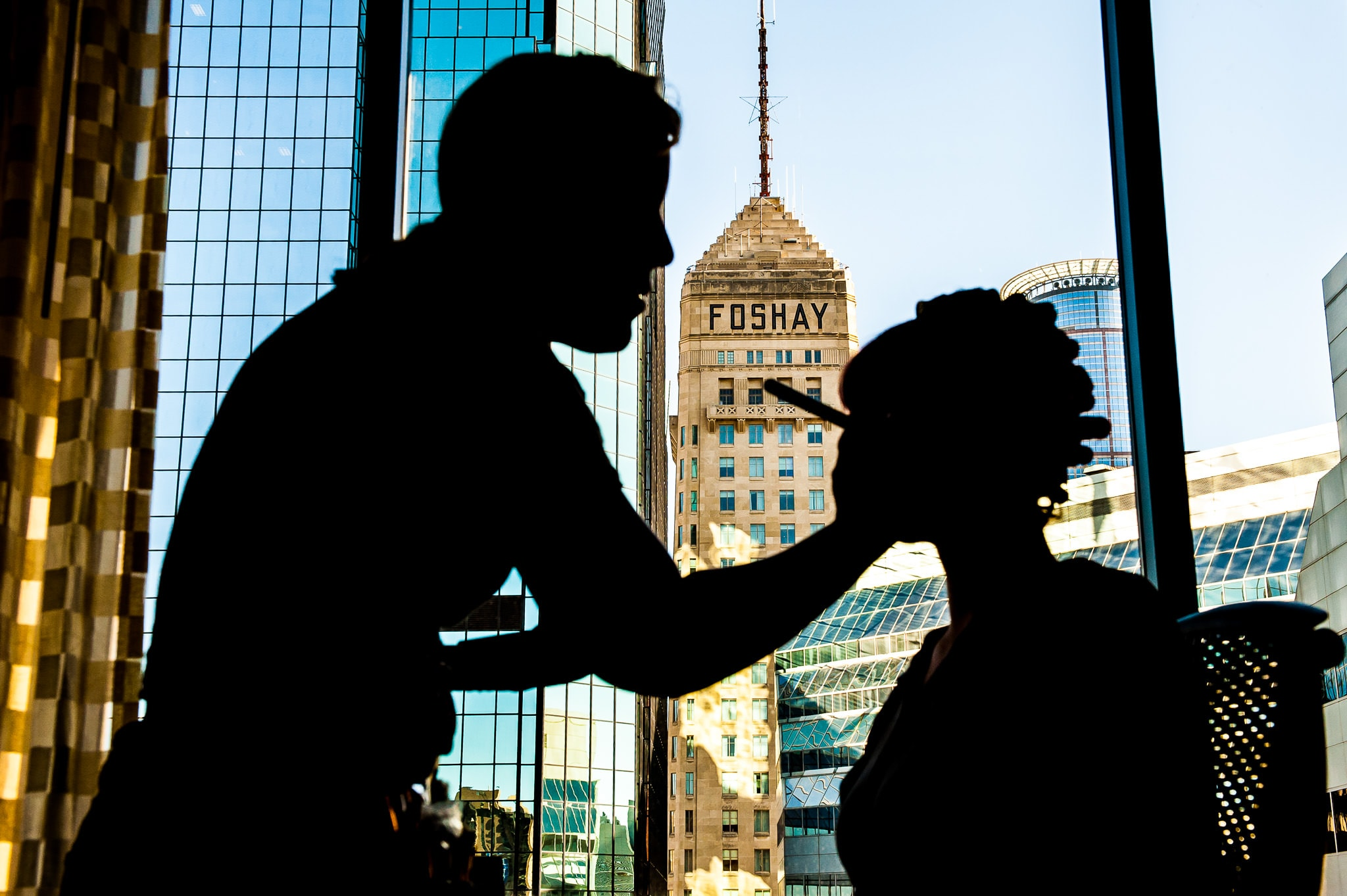 Bride in Silhouette while she gets her makeup done before her wedding with the Foshay Tower and downtown Minneapolis in the background