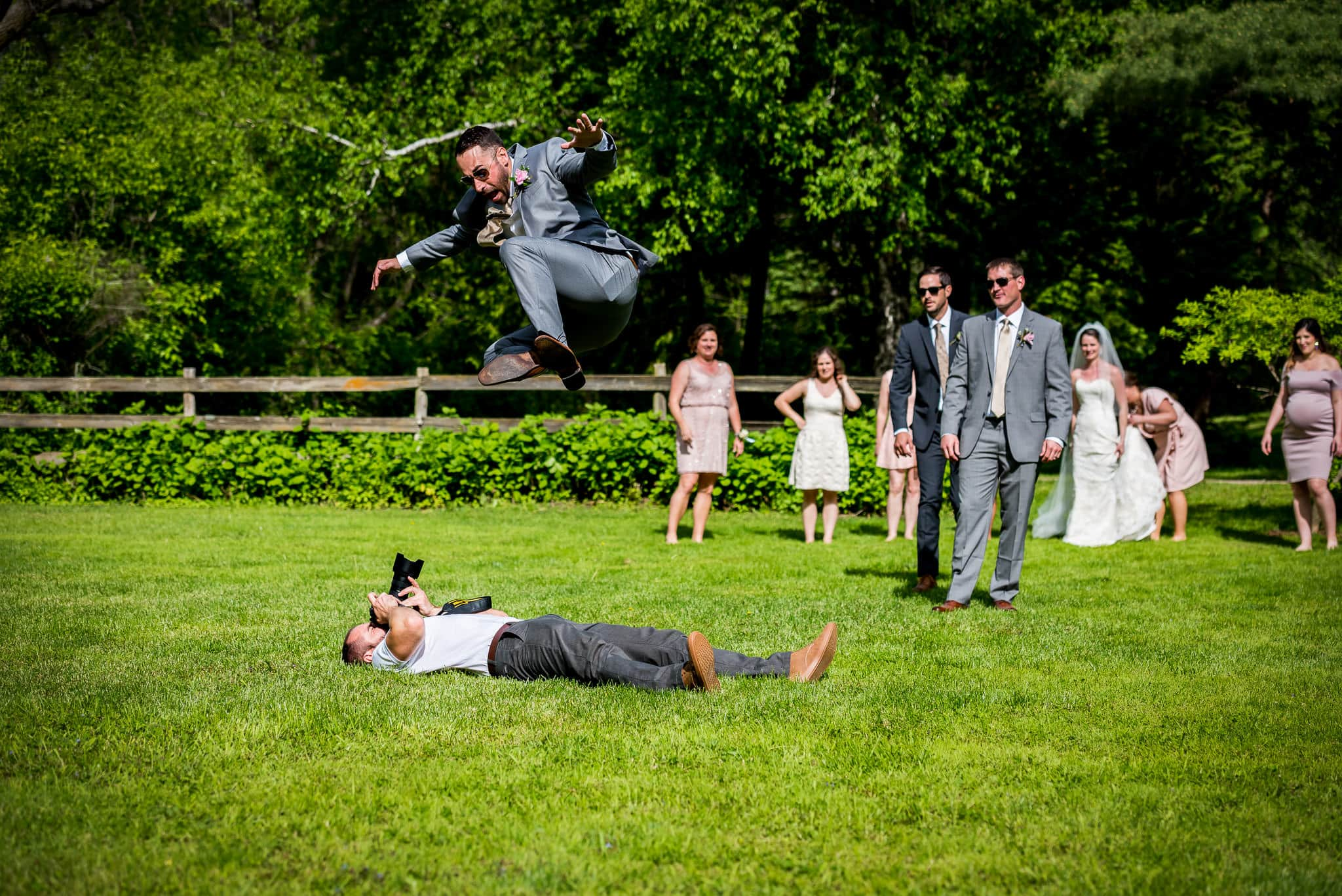 Minneapolis wedding photographer Jackson Tyler Eddy laying on the ground photographing groomsmen jumping over him