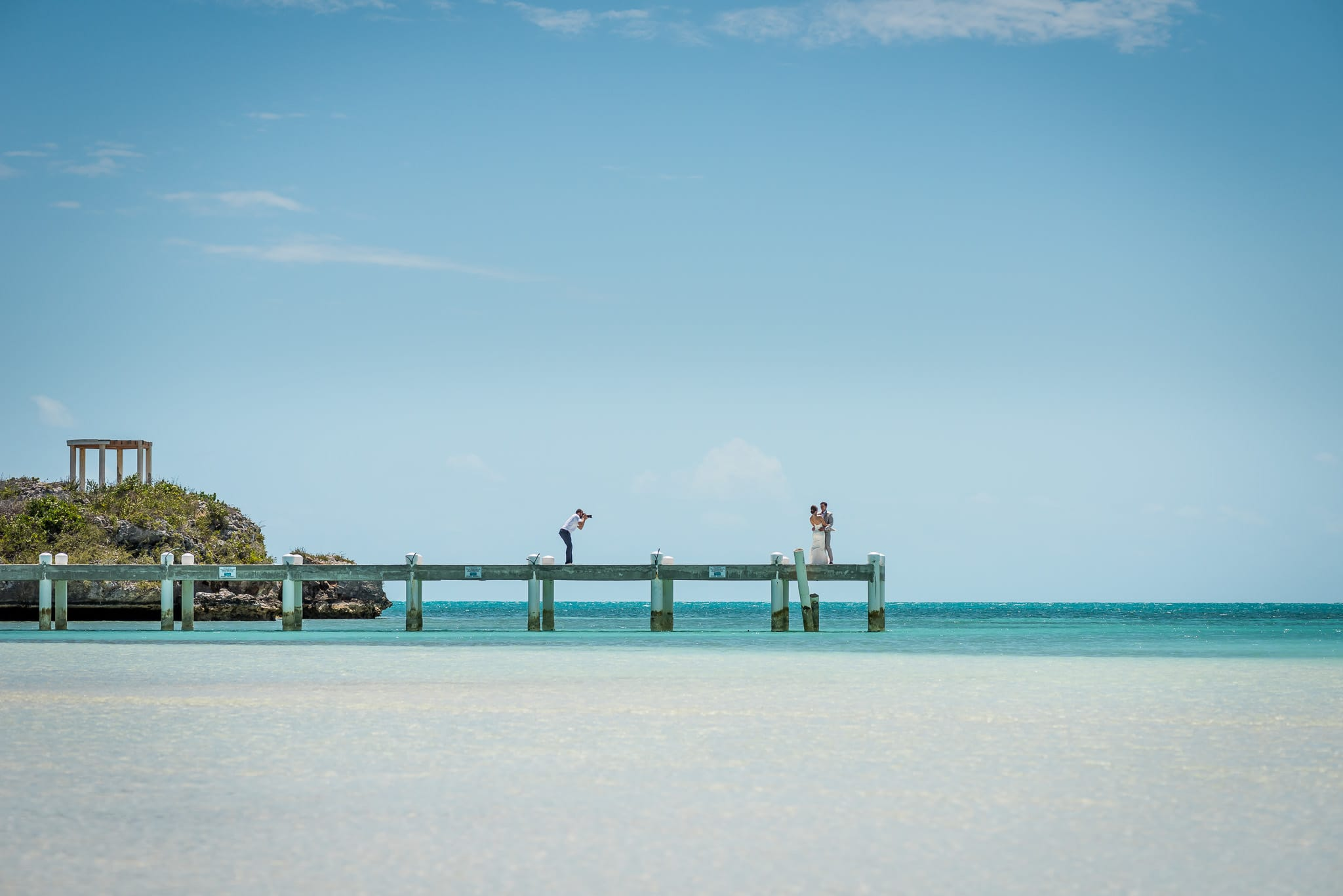Jackson Tyler Eddy of A Frame Forward Photography photographing bride and groom on a long pier in Turks & Caicos