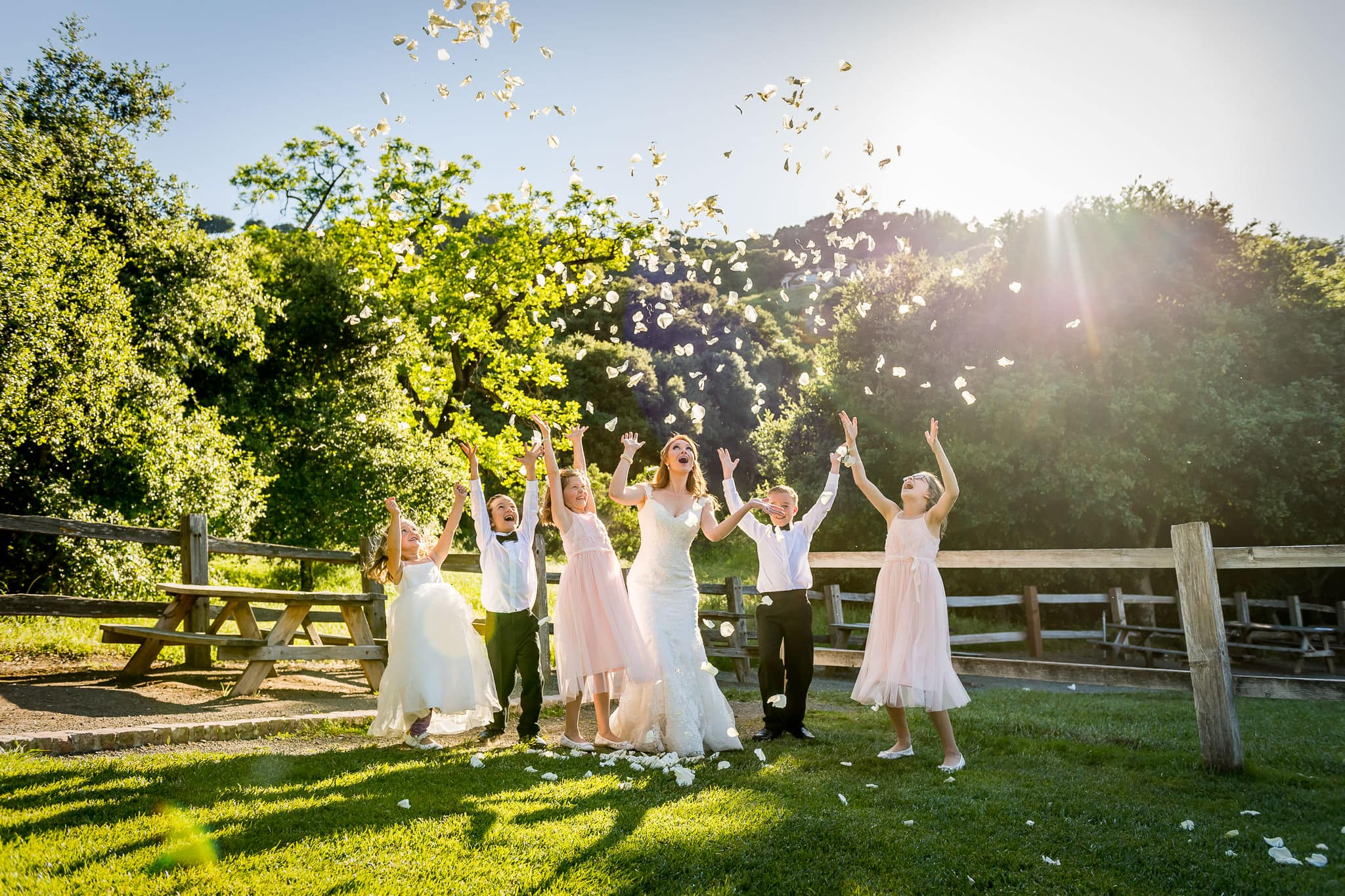 Bride and kids throwing rose pedals into the air