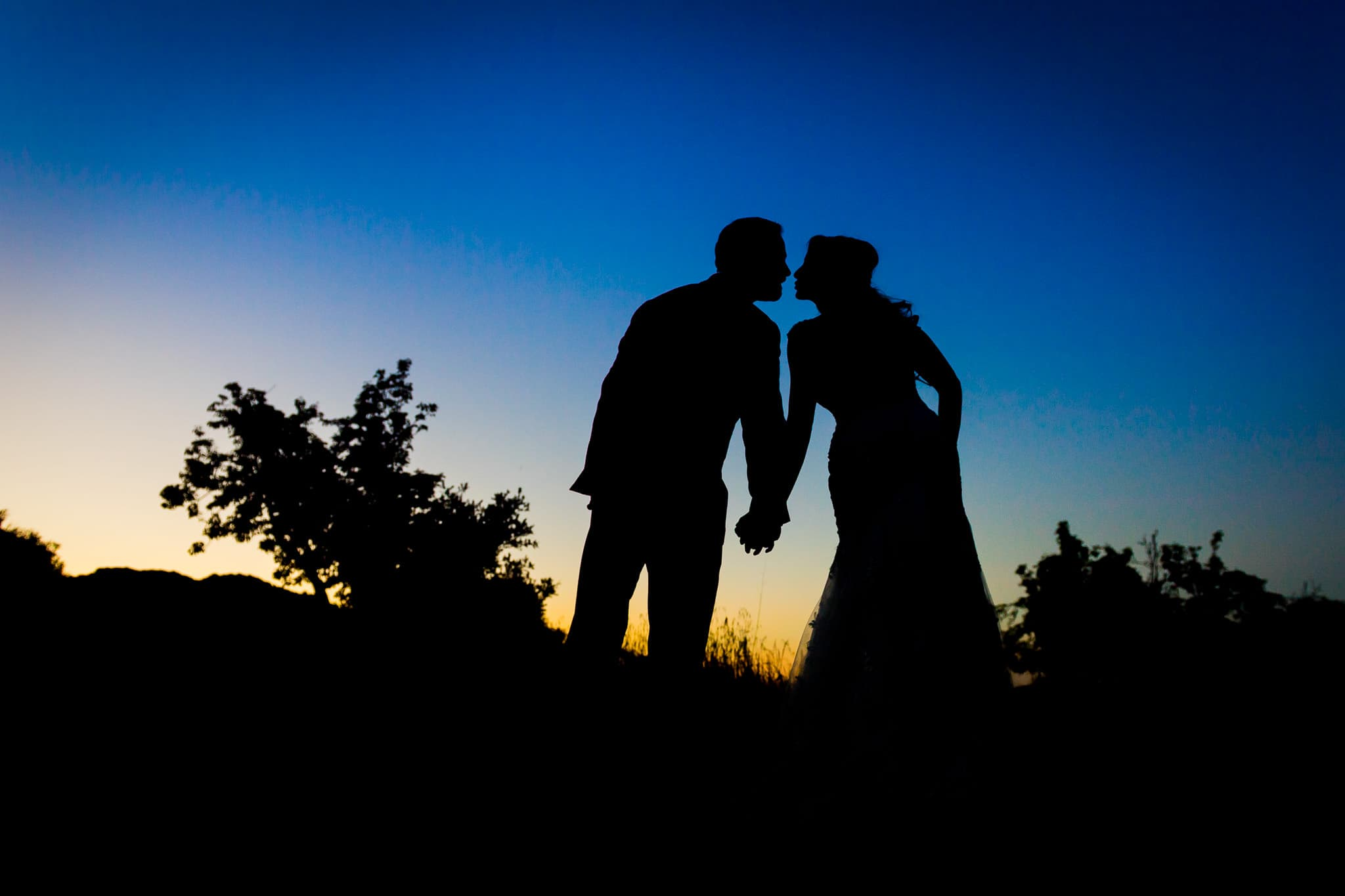 colorful silhouette of bride and groom closing in on a kiss with the sunset behind them