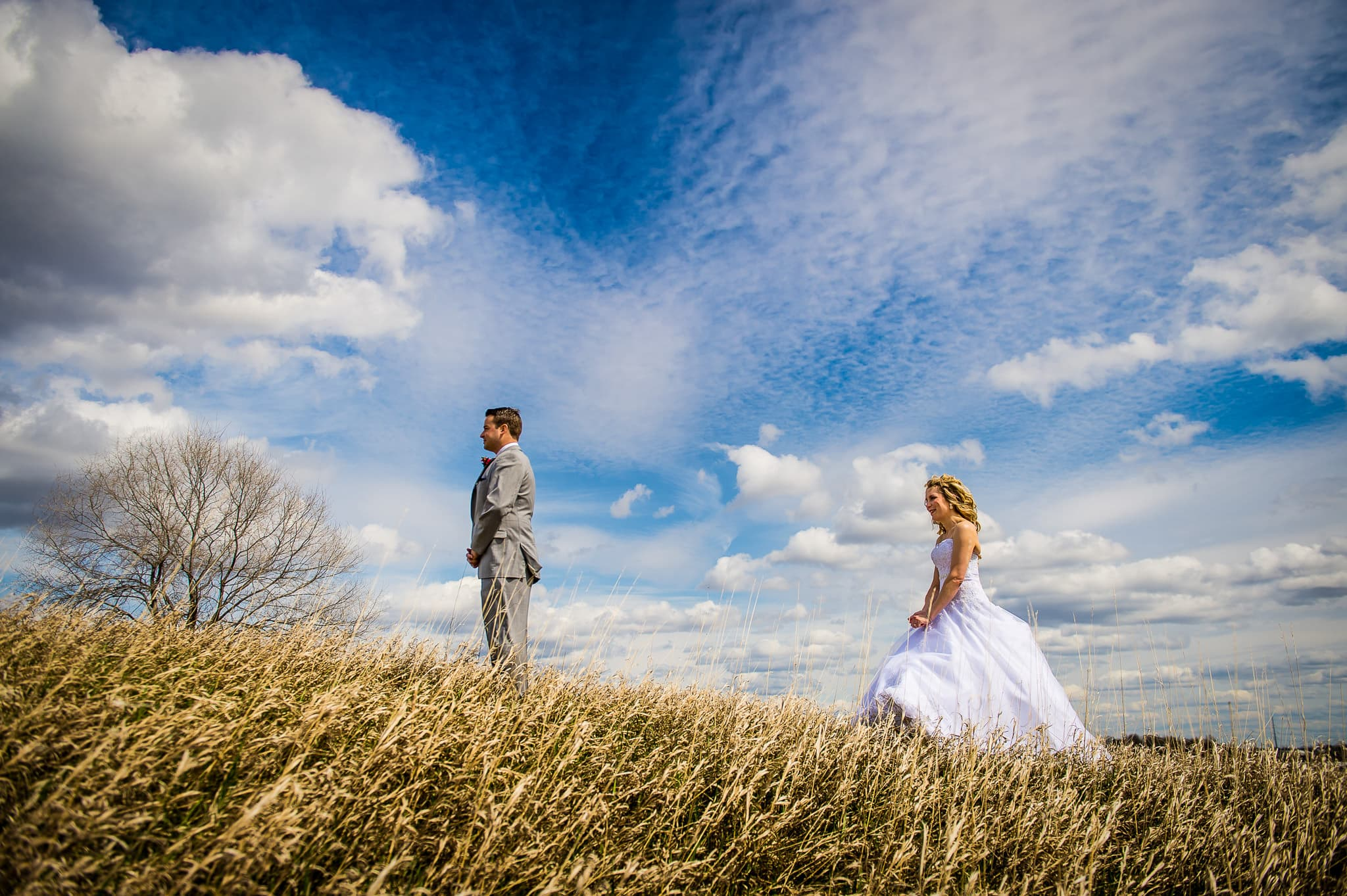 A couple getting ready for their first look on their wedding day in a grassy field with beautiful blue sky and clouds in the background