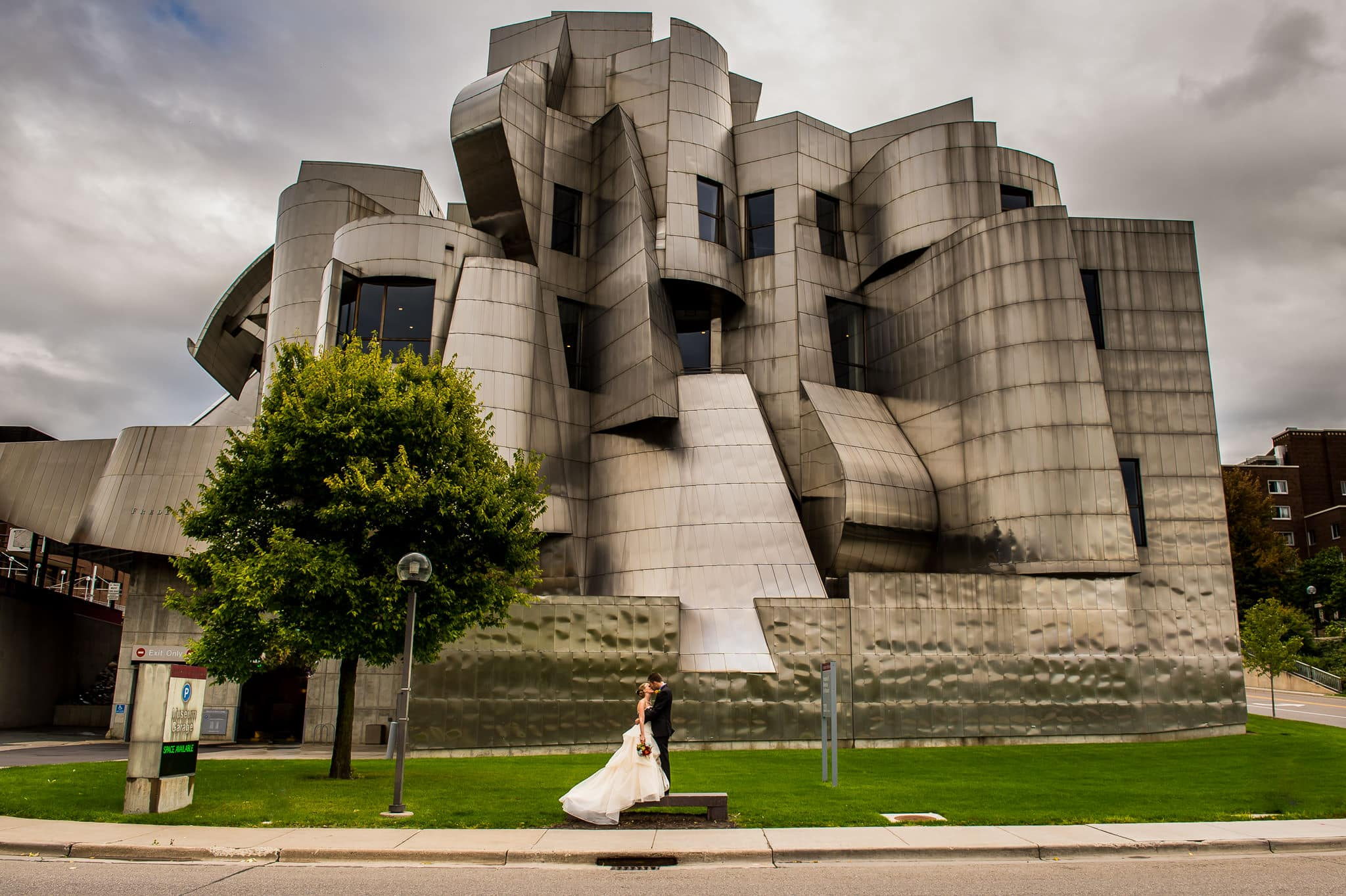 Wide angle shot of a couple kissing in front of the Weisman Art Museum on their wedding day
