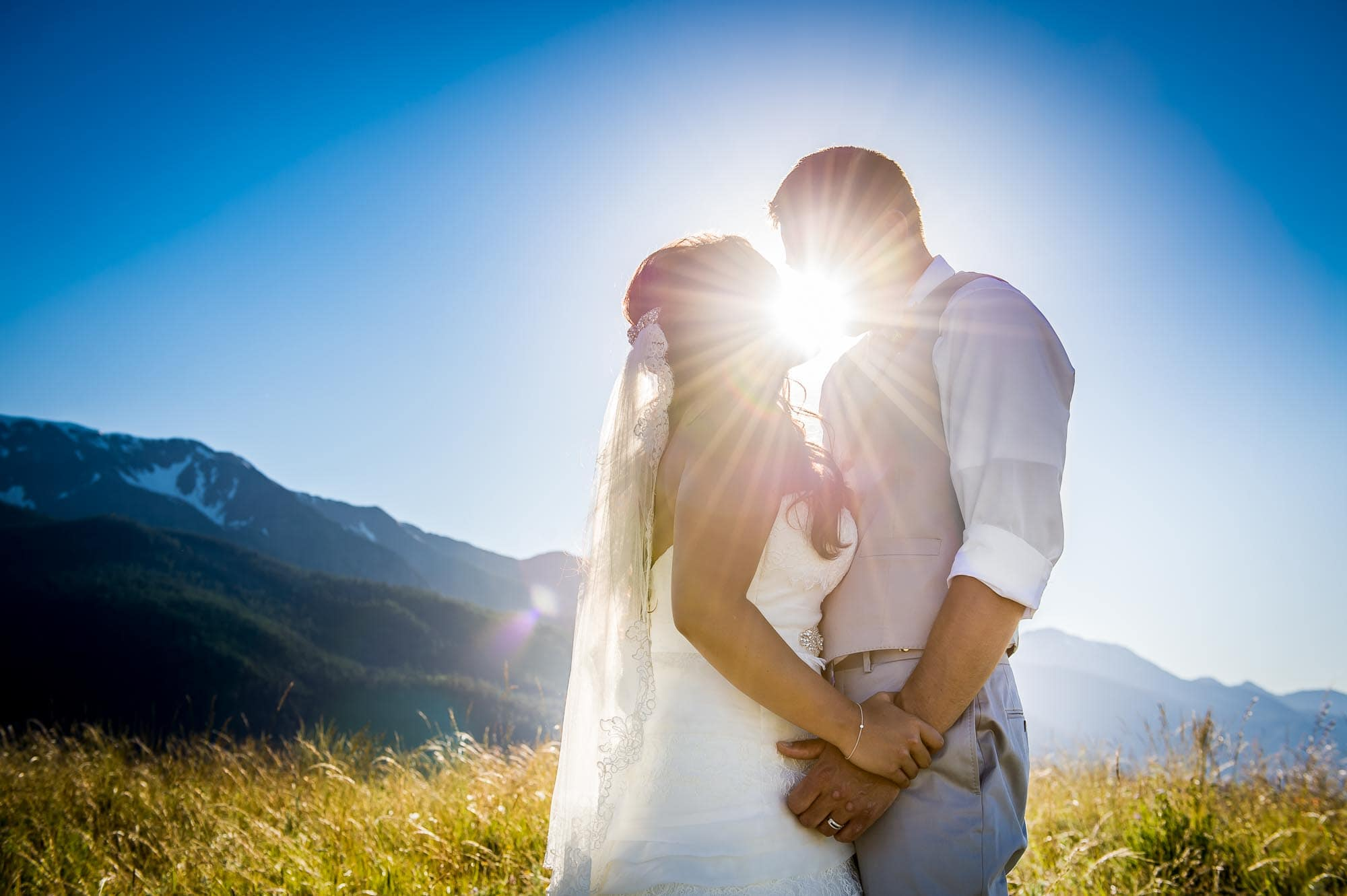 Destination wedding kiss in Joseph, Oregon with sun-flare and the Wallowa mountains in the background
