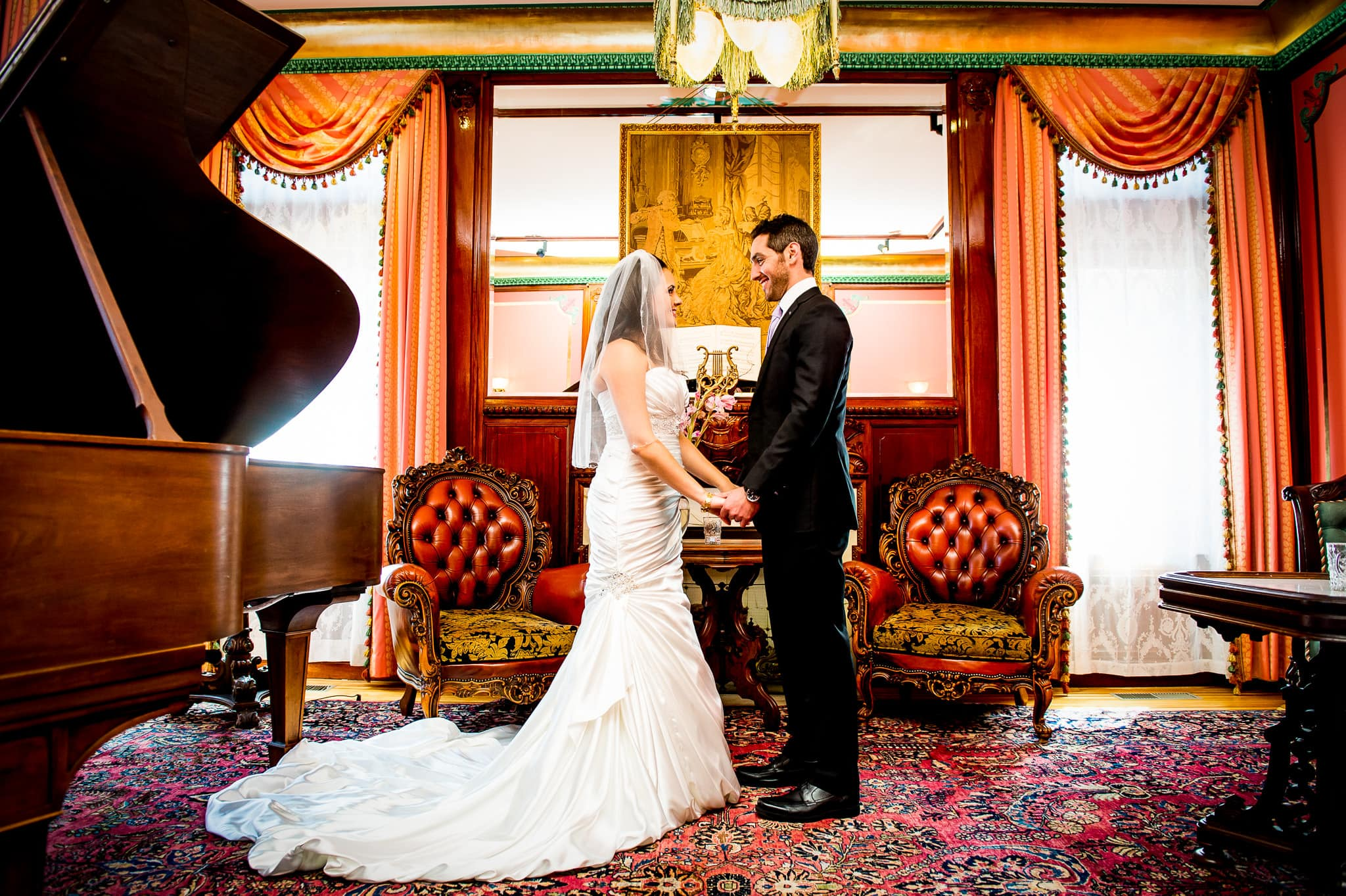 Bride and Groom hold hands in the luxurious and colorful piano room at the Van Dusen Mansion