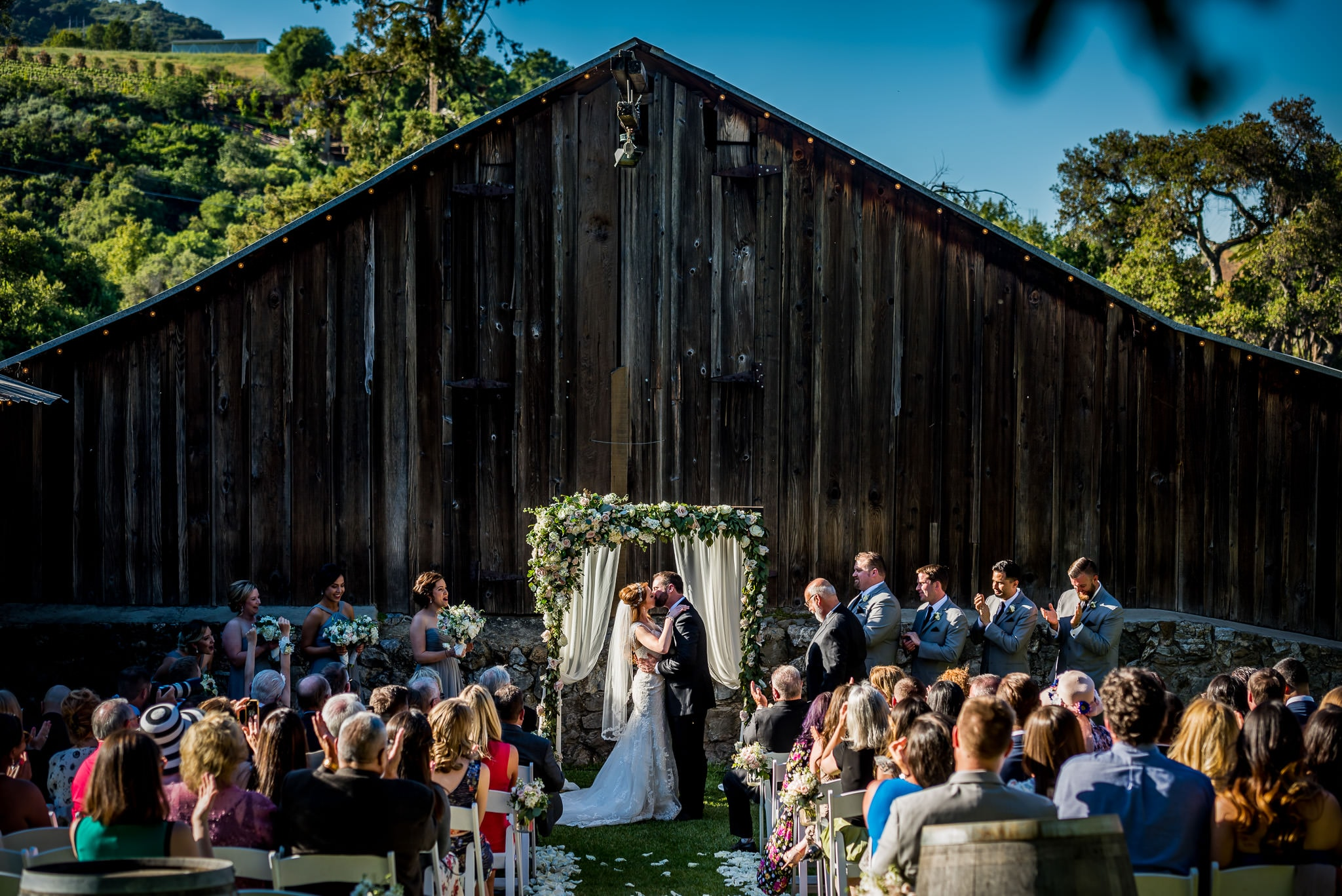 Wedding ceremony kiss in front of weathered old barn at the Picchetti Wintery in Cupertino, California