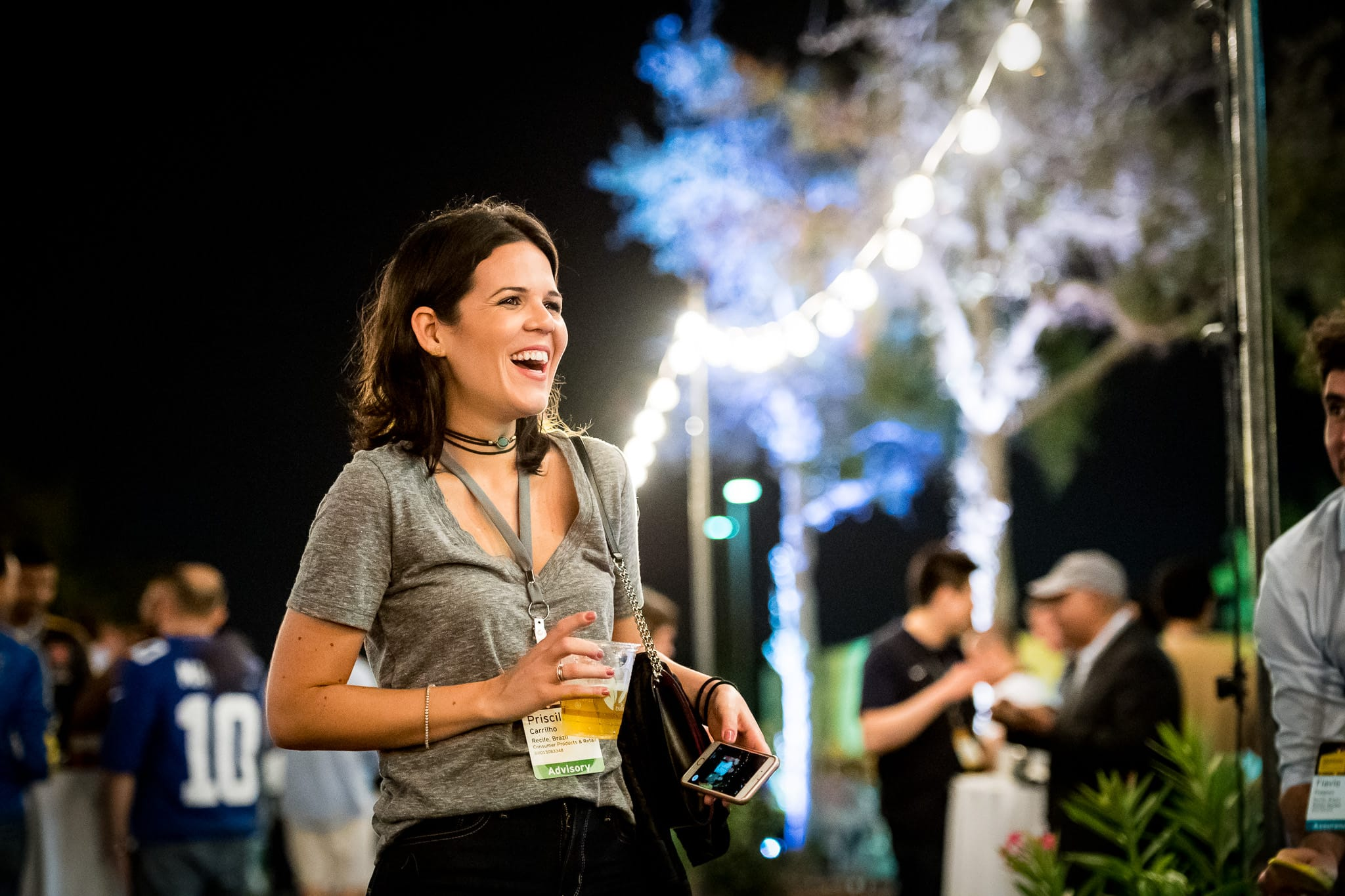 Female employee laughing with colorful lights in the background at EY's annual corporate event