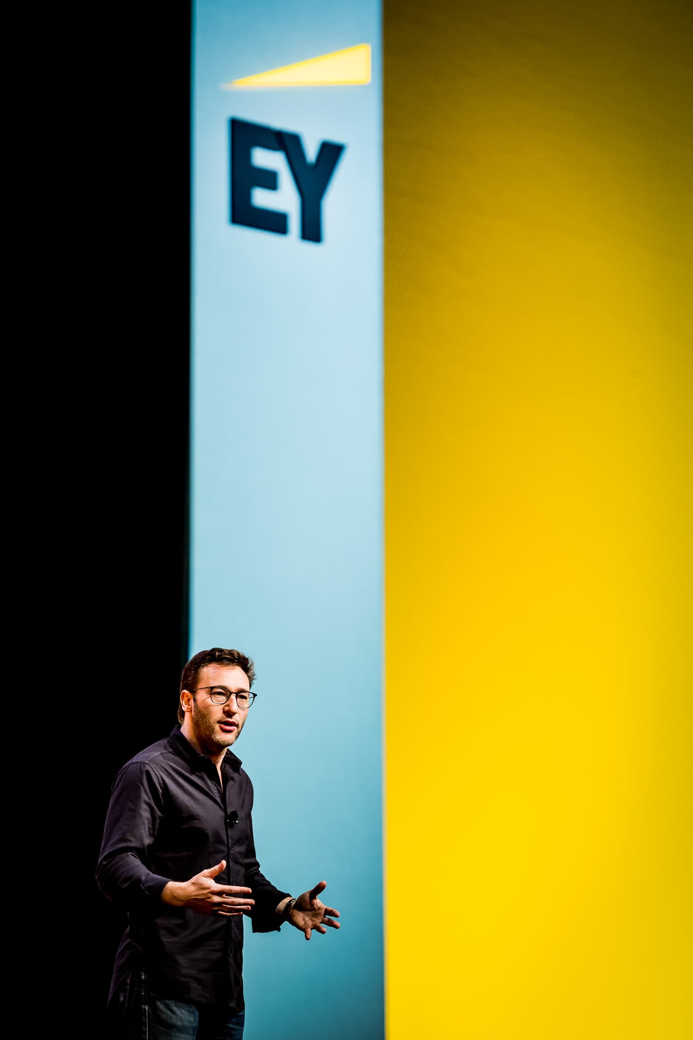 Vertical and colorful photo of Simon Sinek speaking at the EY Milestones Corporate Event