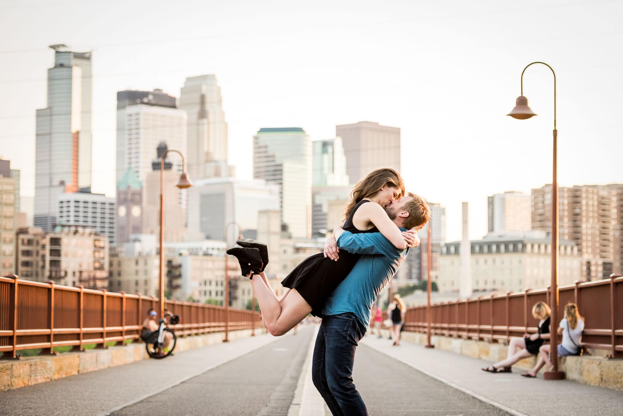 Huge hug and kiss on the Stone Arch Bridge with the Minneapolis skyline in the background