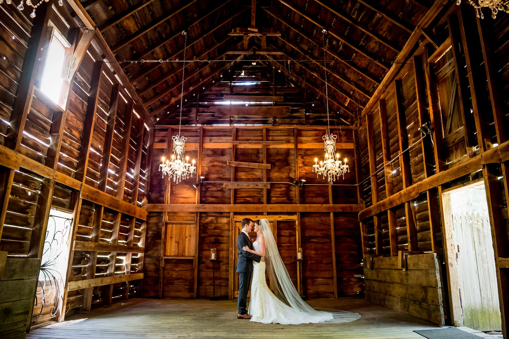 Bride and Groom hold each other closely inside the barn at Camrose Hill Flower Farm