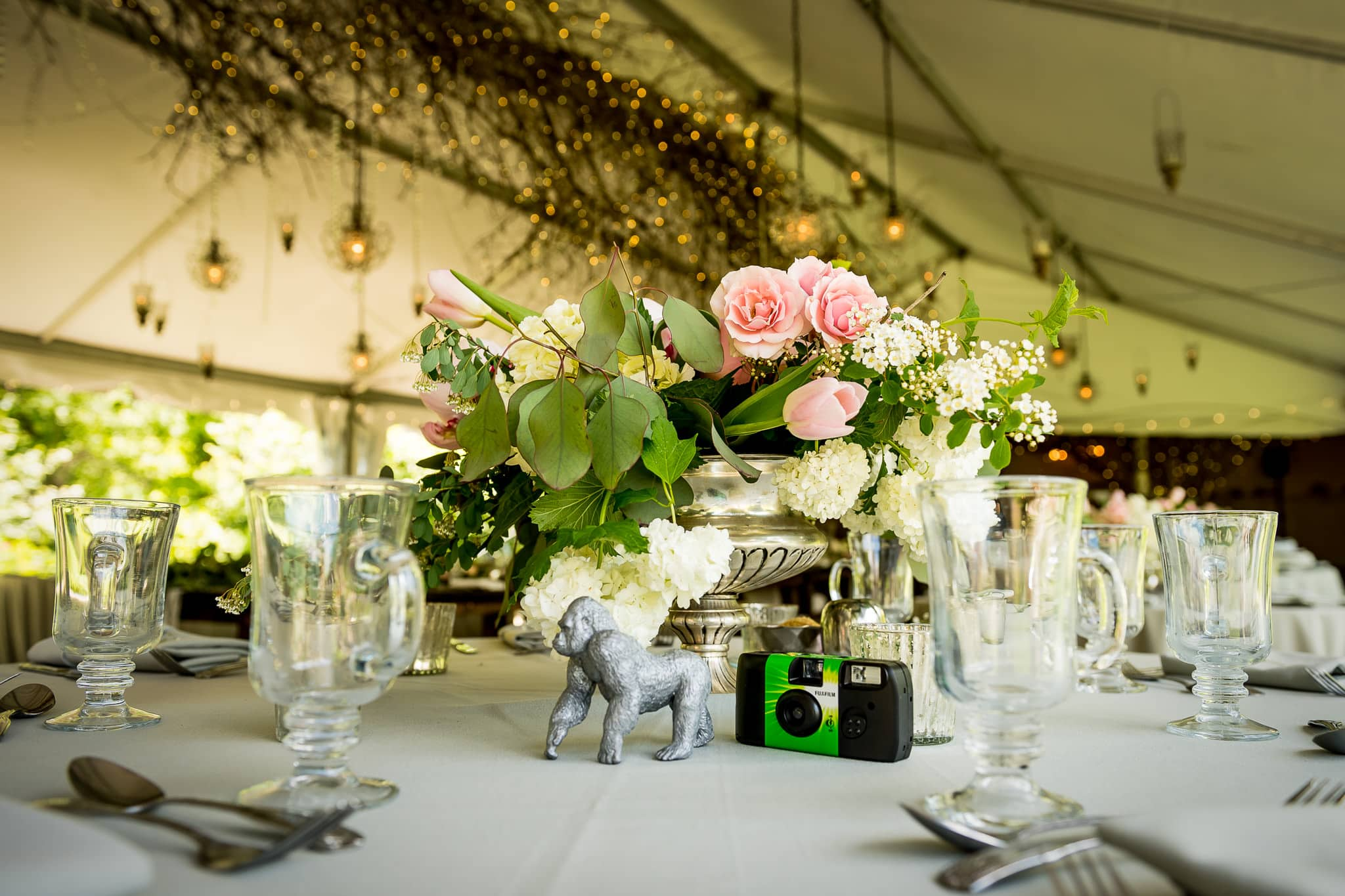 Beautiful floral centerpieces, toy animals, and disposable cameras sitting on the wedding reception tables at Camrose Hill Flower Farm