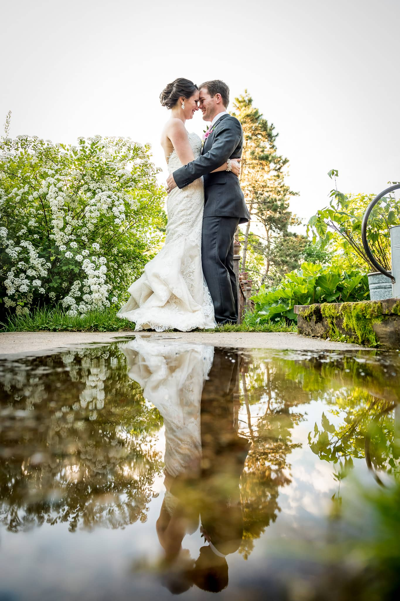 Creative Bride and Groom symmetrical reflection image in rain water puddle at Camrose Hill Flower Farm