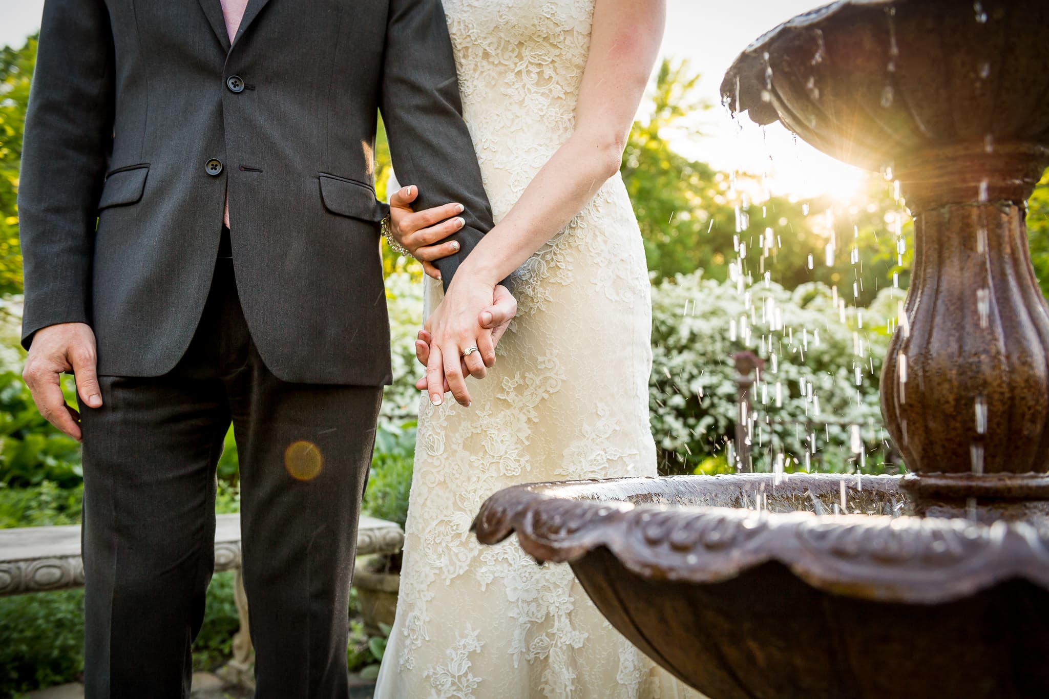 Bride & Groom holding hands in front of Camrose Hill's water fountain with sun flare shooting through the water
