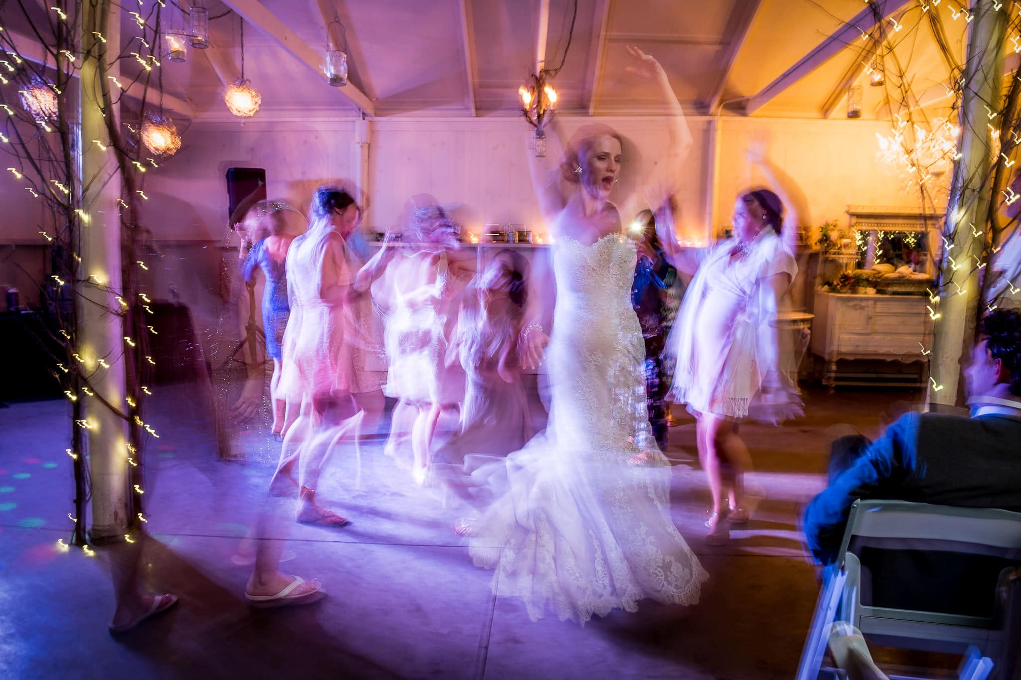 Rear-sync flash photograph of bride twirling on the dance floor at Camrose Hill Flower Farm