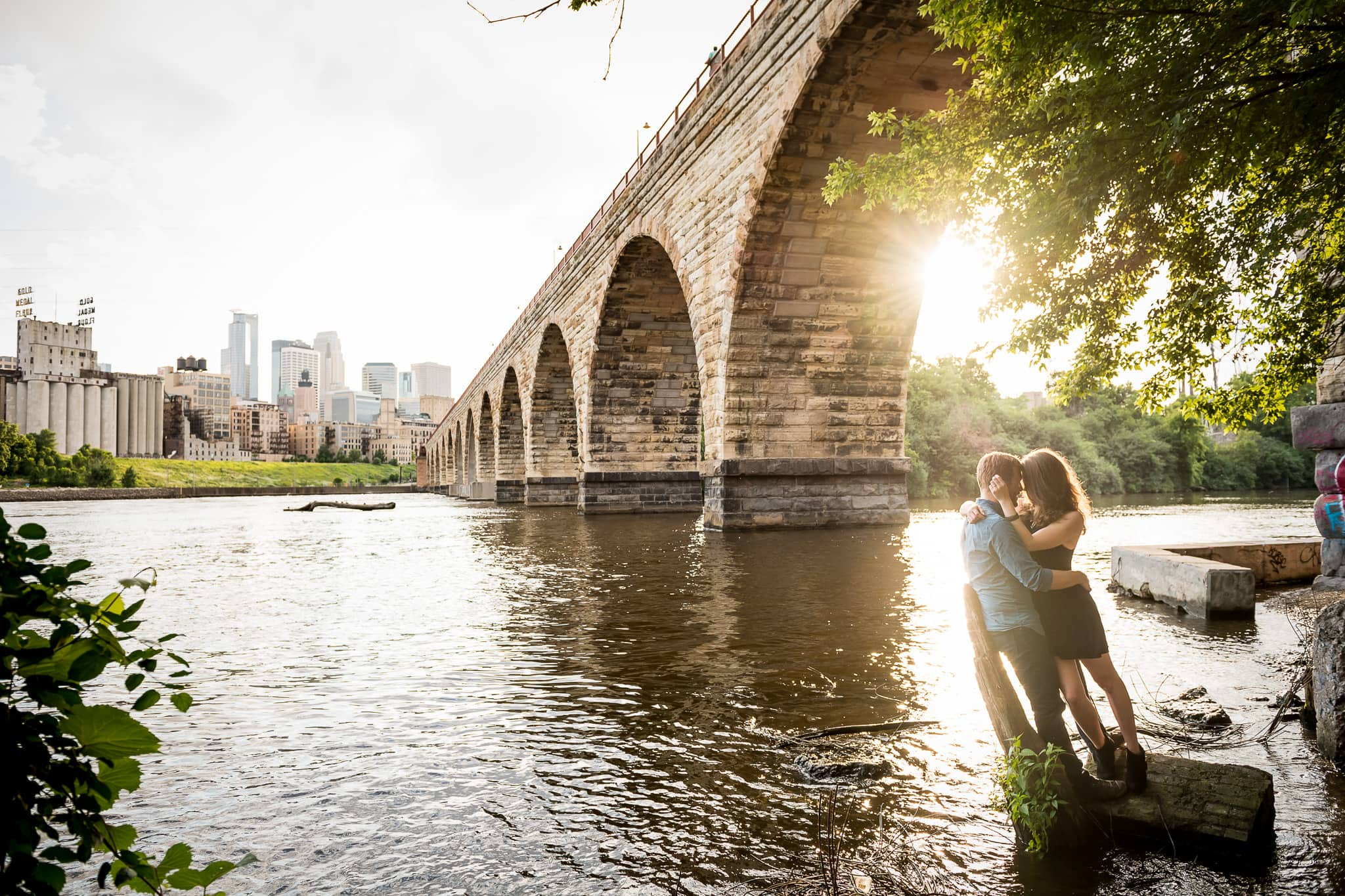 Engagement photo of couple snuggling by the Mississippi River by the Stone Arch Bridge in Minneapolis