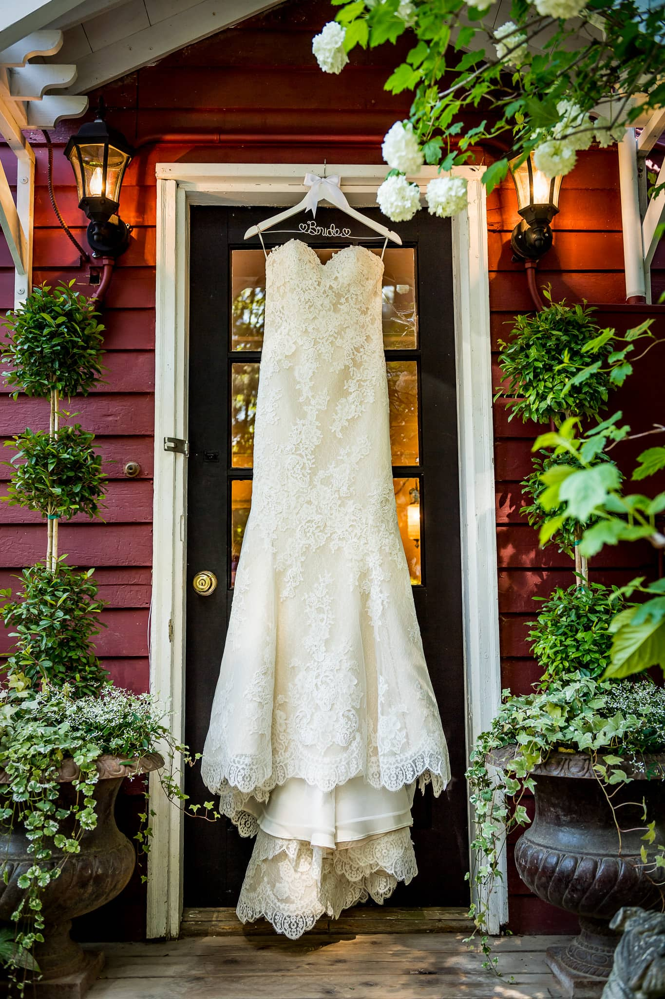 Bride's wedding dress hanging on the cottage house at Camrose Hill Flower Farm