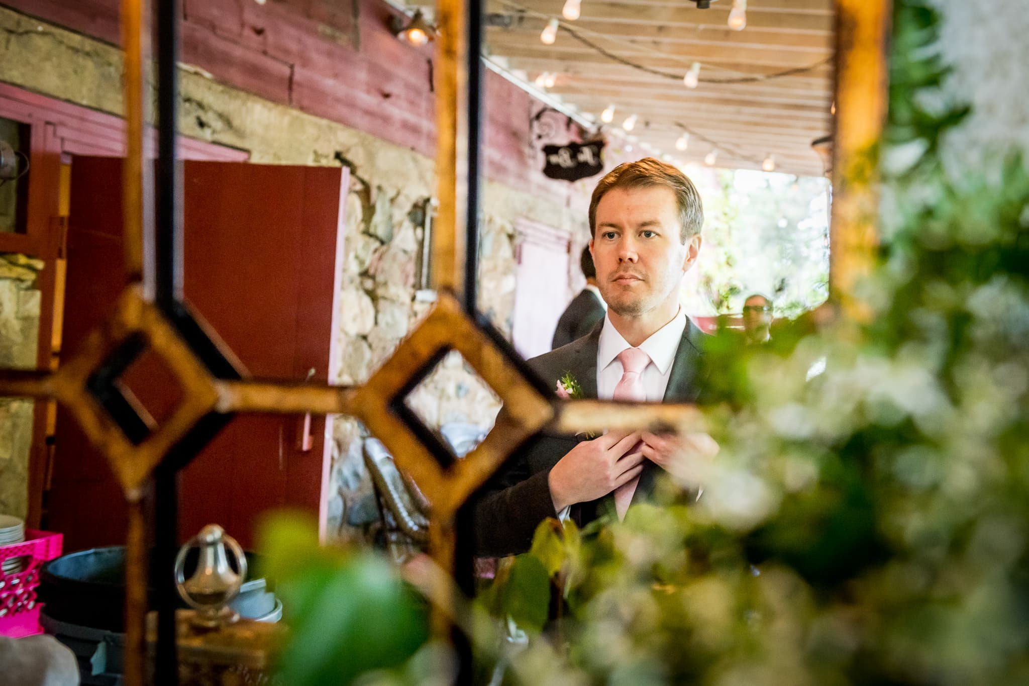 Cool mirror photo of groom getting ready in the groomsmen quarters at Camrose Hill Flower Farm