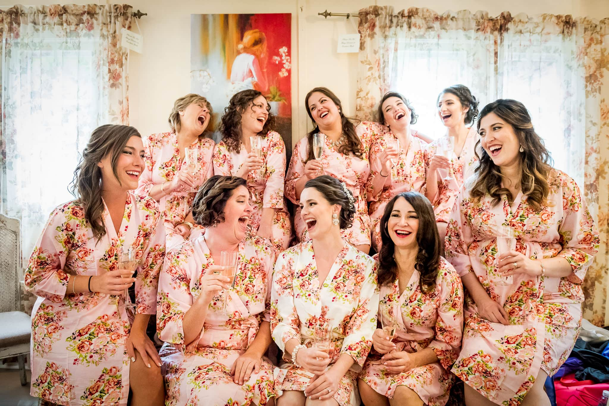 Bridesmaids candid group photo laughing and drinking inside the Camrose Hill bridal cottage house