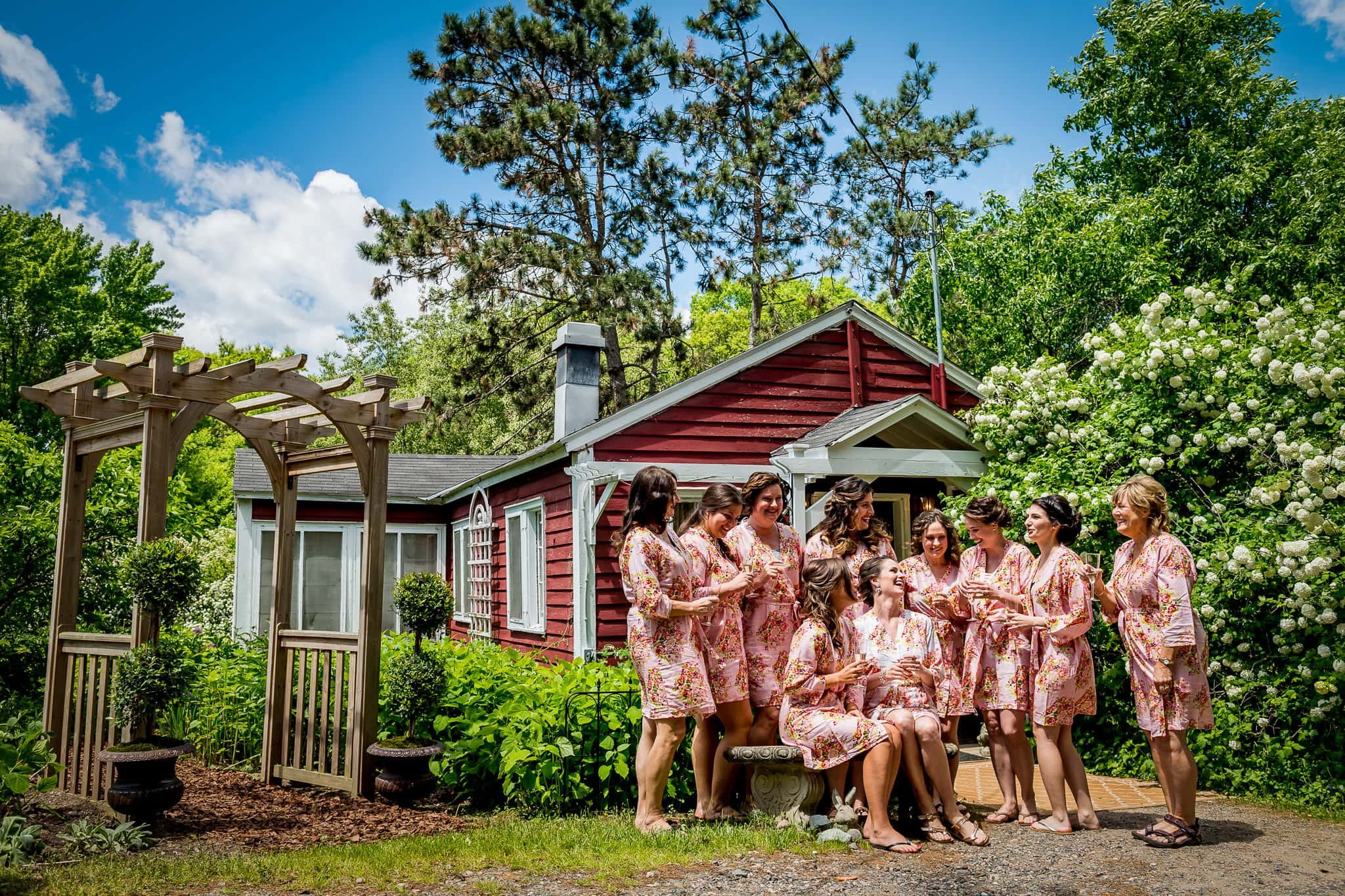 Bride and Bridesmaids in their robes laughing in front of the Camrose Hill Flower Farm bridal cottage house