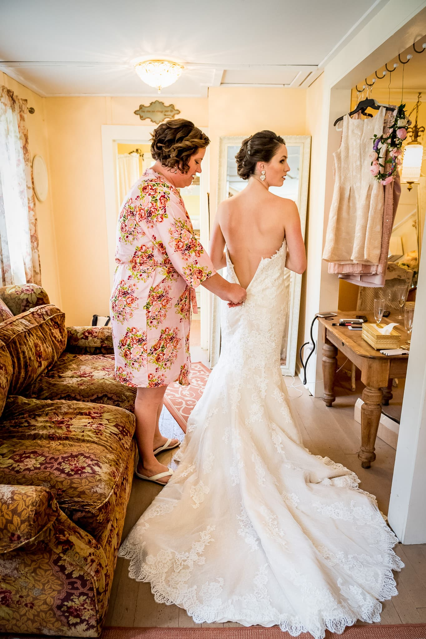 Bride's sister zips up her wedding dress at Camrose Hill Flower Farm wedding