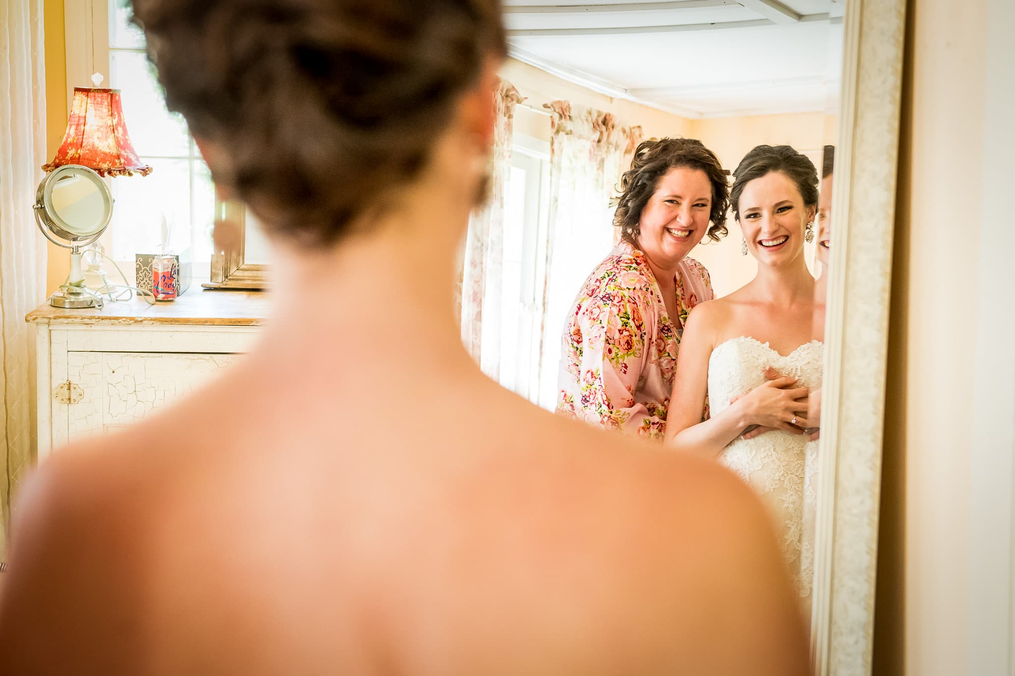 Mirror reflection image of bride and sister sharing a beautiful moment at Camrose Hill