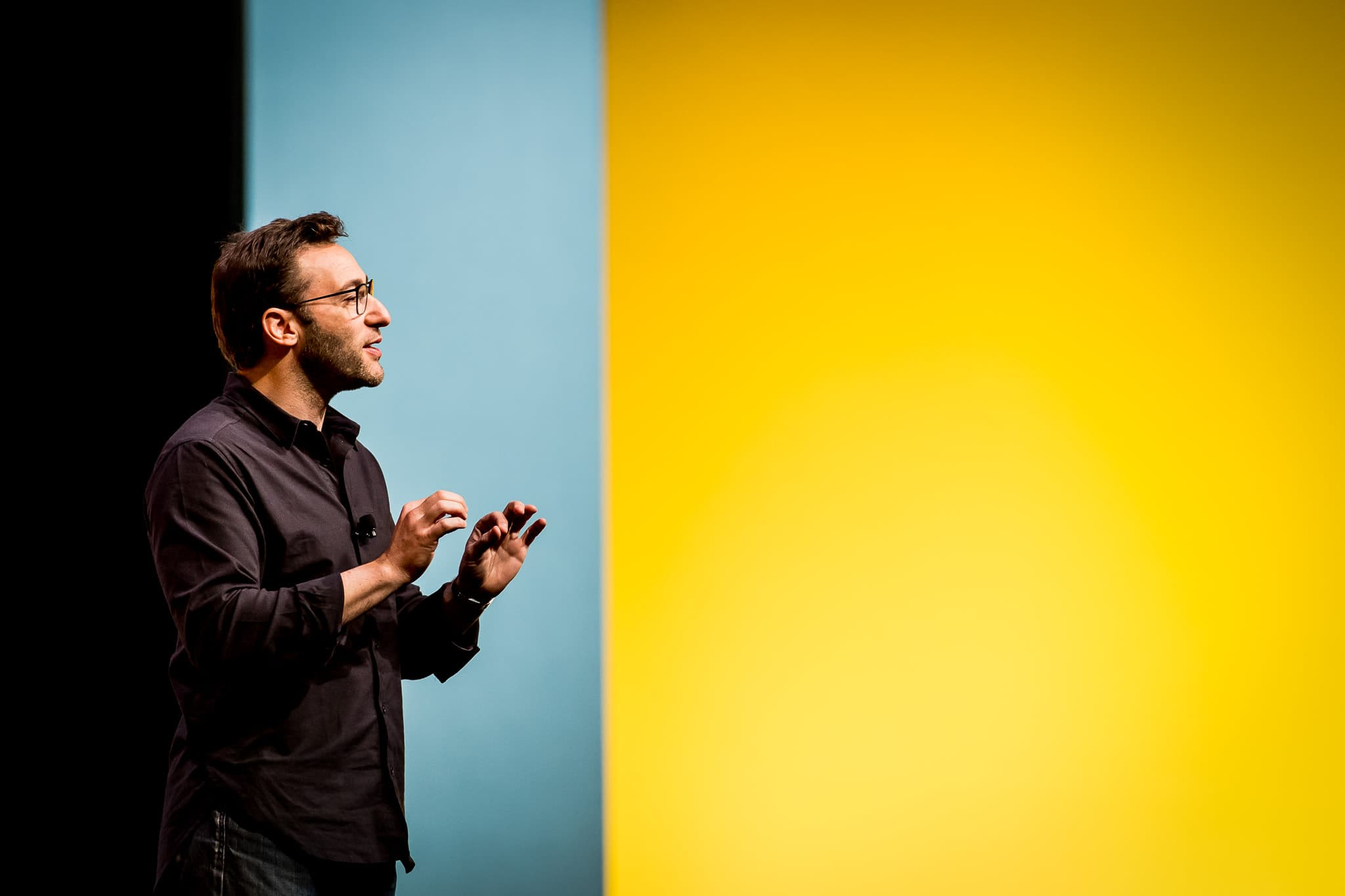 Simon Sinek giving Keynote Speech for EY employees in Orlando, FL with colorful background