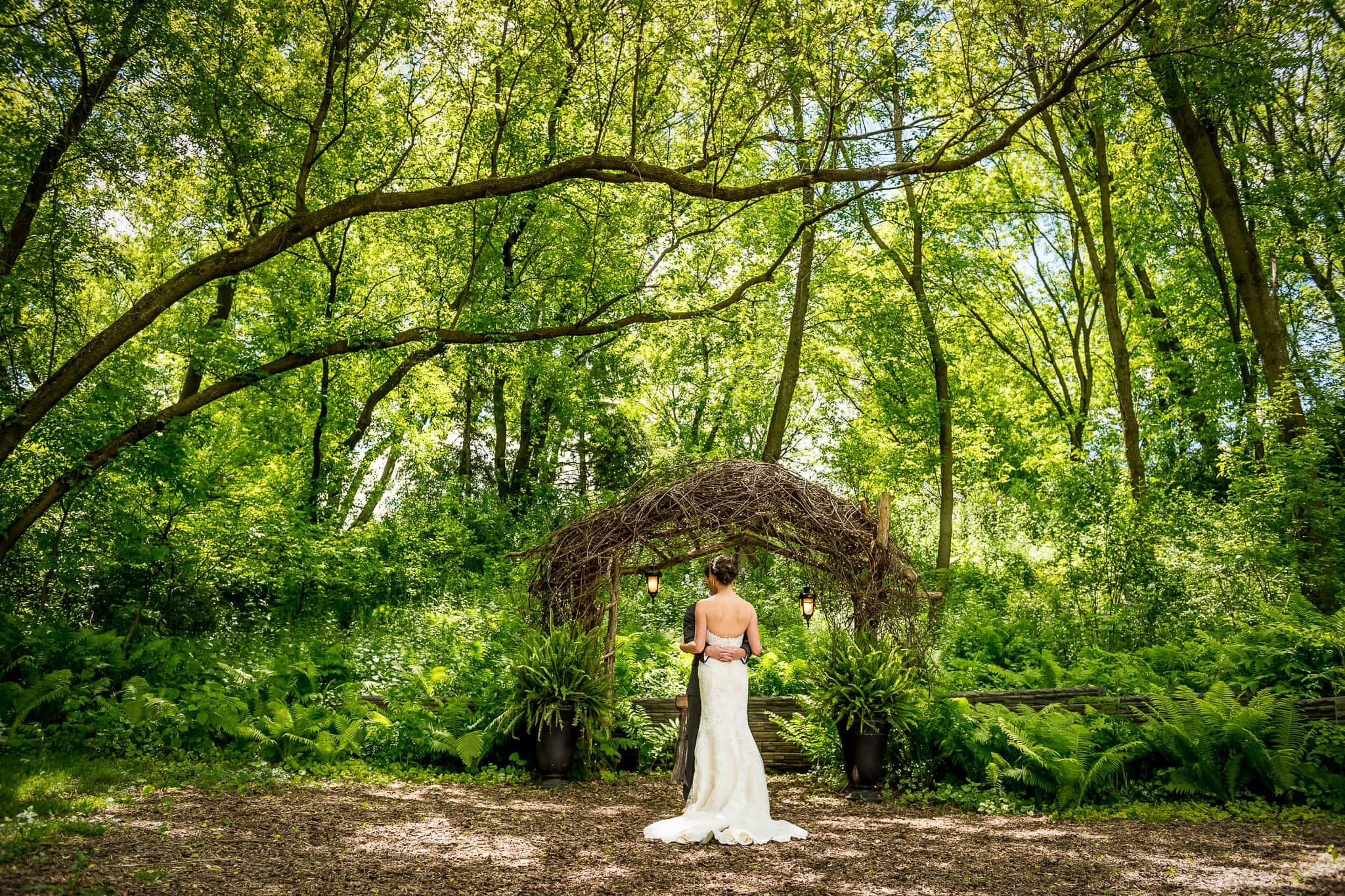 Wide shot of bride and groom inside the Fairy Glen outdoor space at Camrose Hill Flower Farm