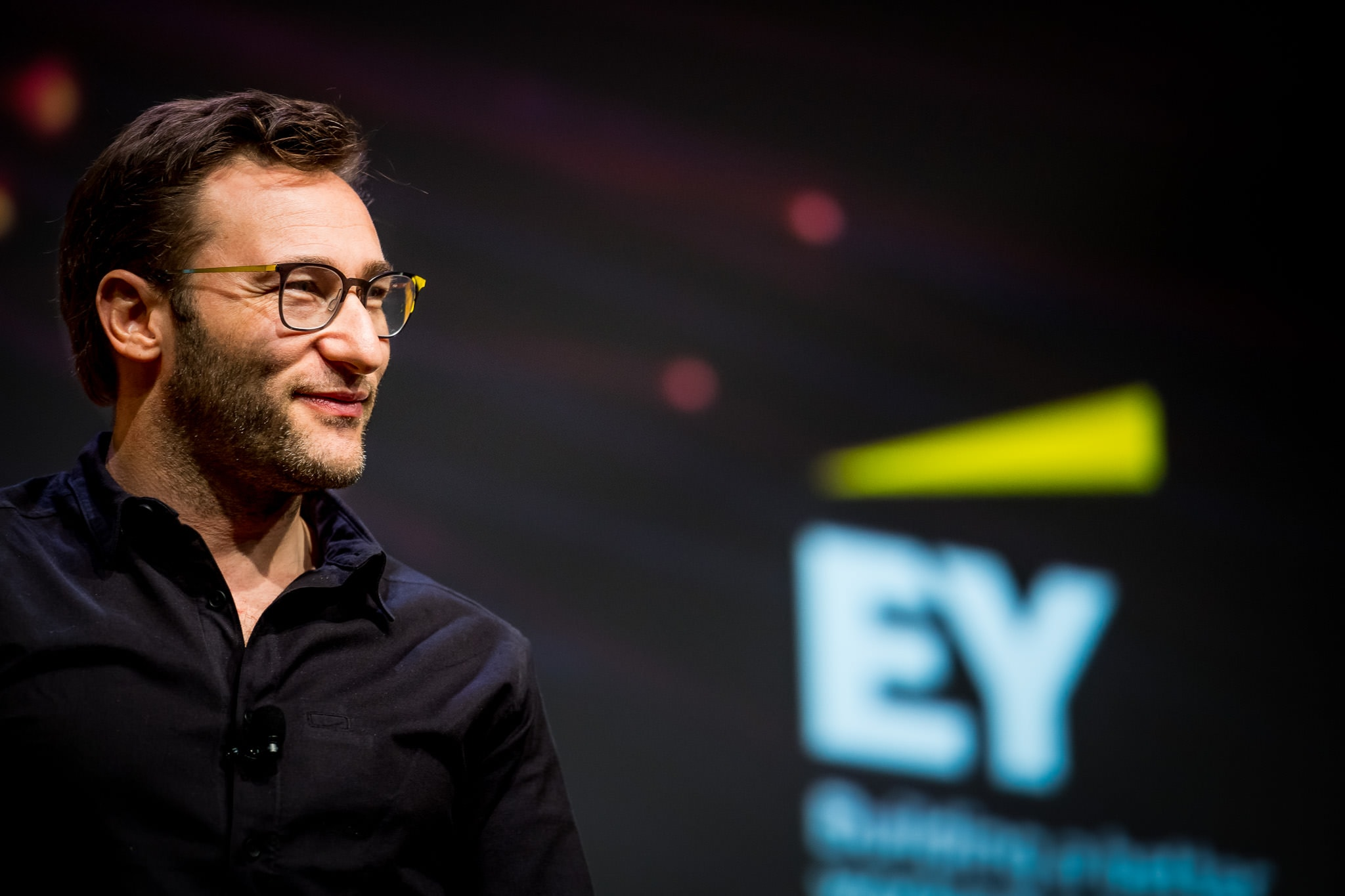 Simon Sinek smiles at the crowd of EY employees during his speech