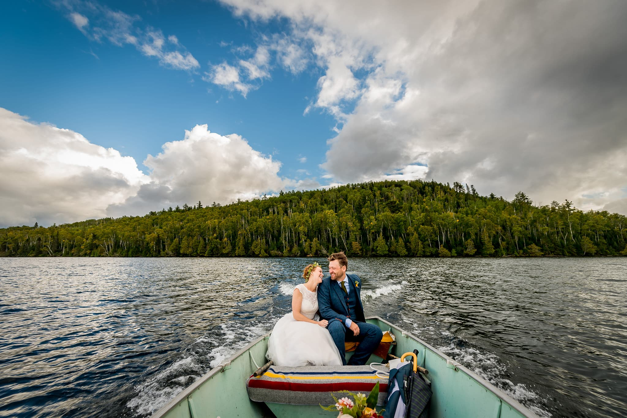 Minneapolis Bride and Groom driving a small fishing boat on their wedding day on a Minnesota lake