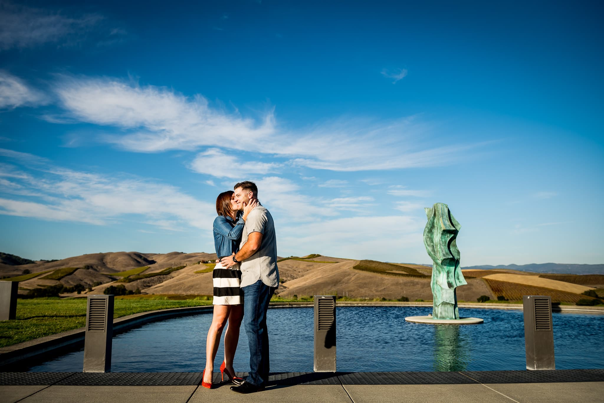Engaged woman kisses her fiancé on the cheek at Artesa Winery in Napa Valley