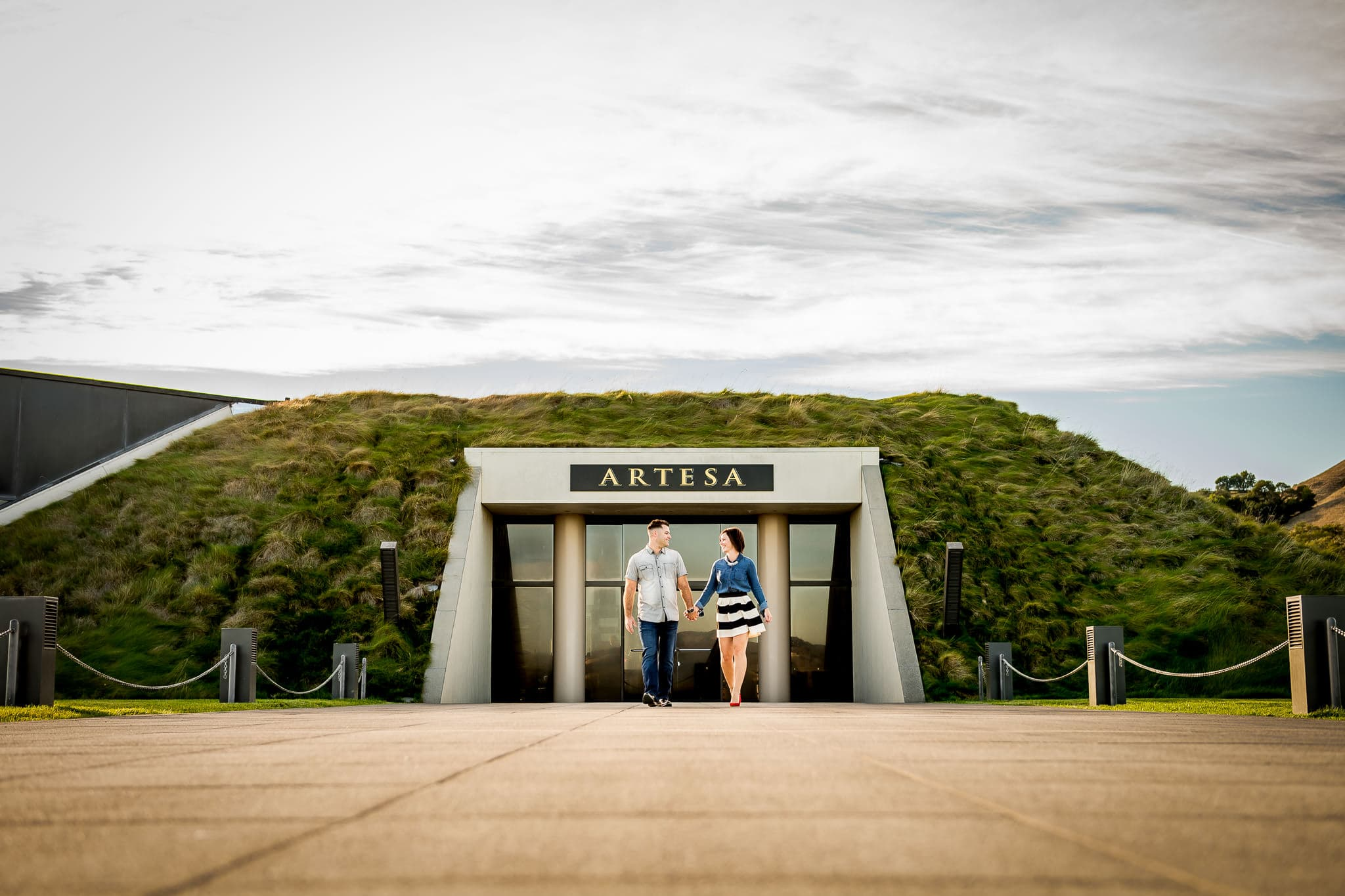An engaged couple walking together near the entrance of the bunker-like building at Artesa Winery in Napa Valley