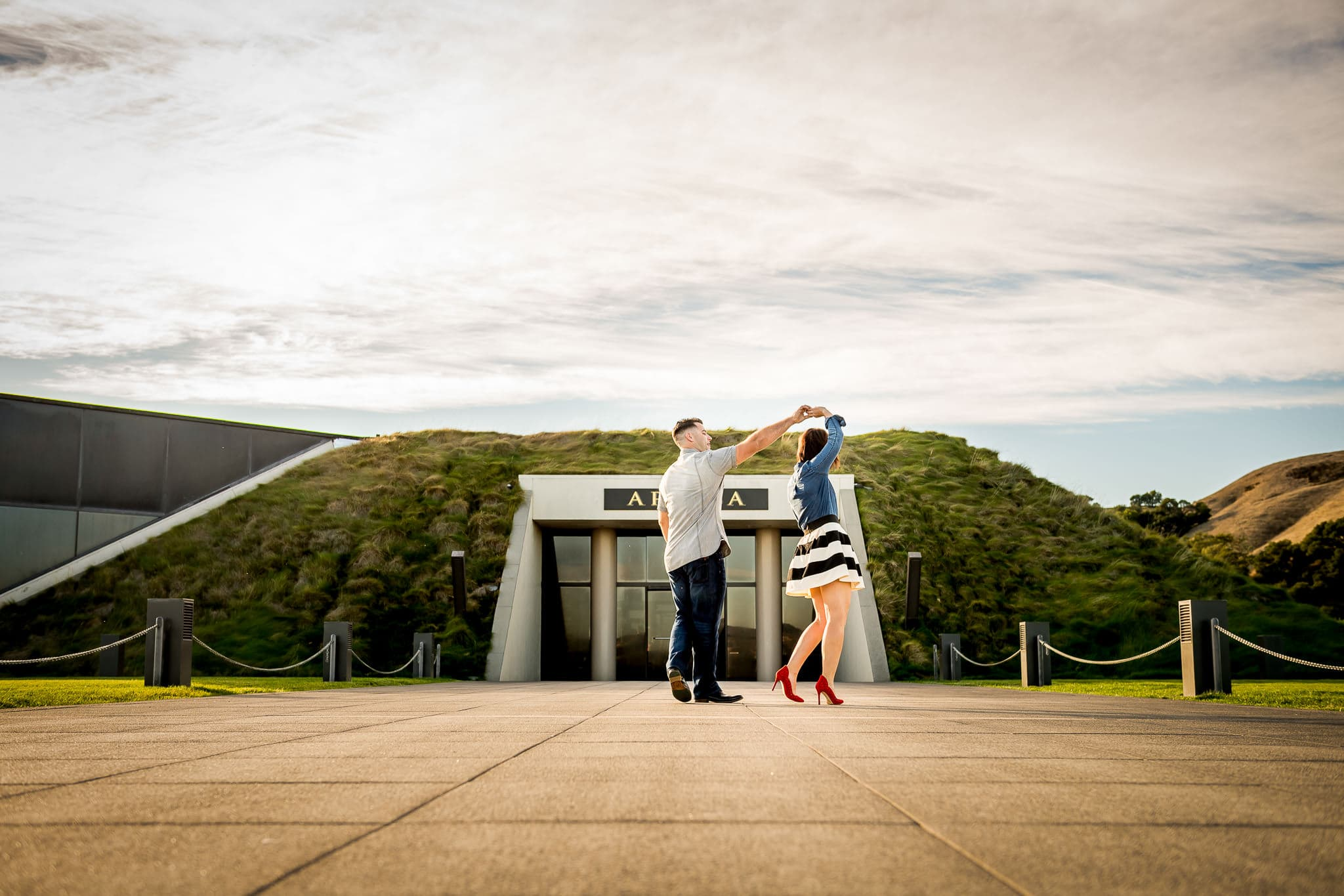 An engaged couple dancing near the entrance of the bunker-like building at Artesa Winery in Napa Valley