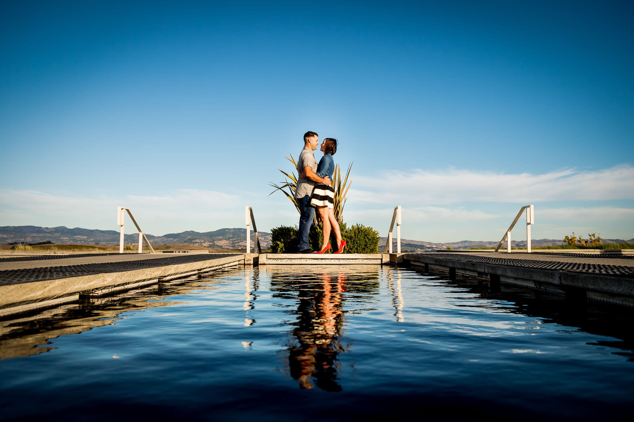 An engaged couple holding each other close with their reflection rippling over the water at Artesa Winery in Napa Valley