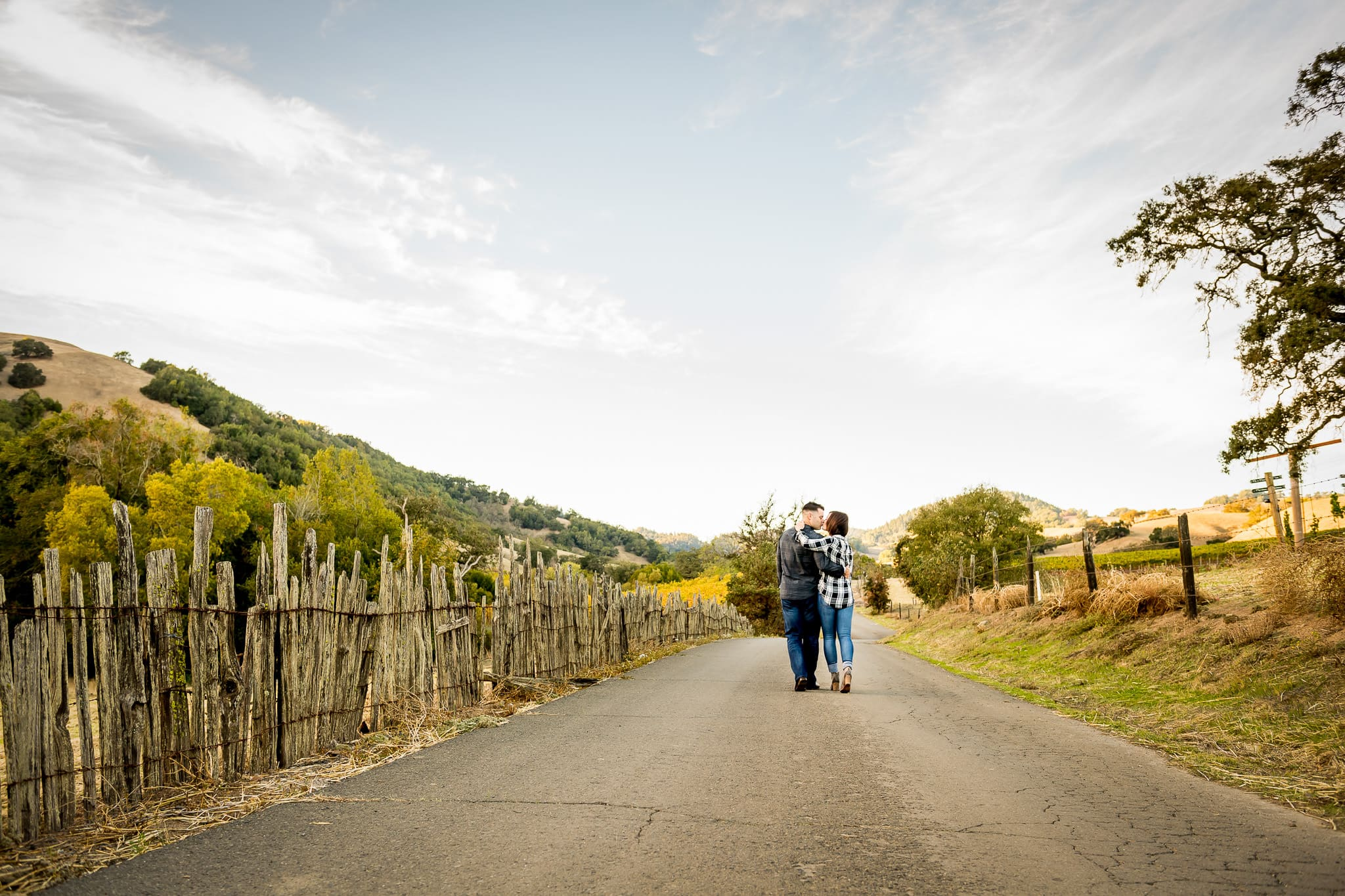 Wide shot of an engaged couple sharing a kiss on a small road running through Napa Valley