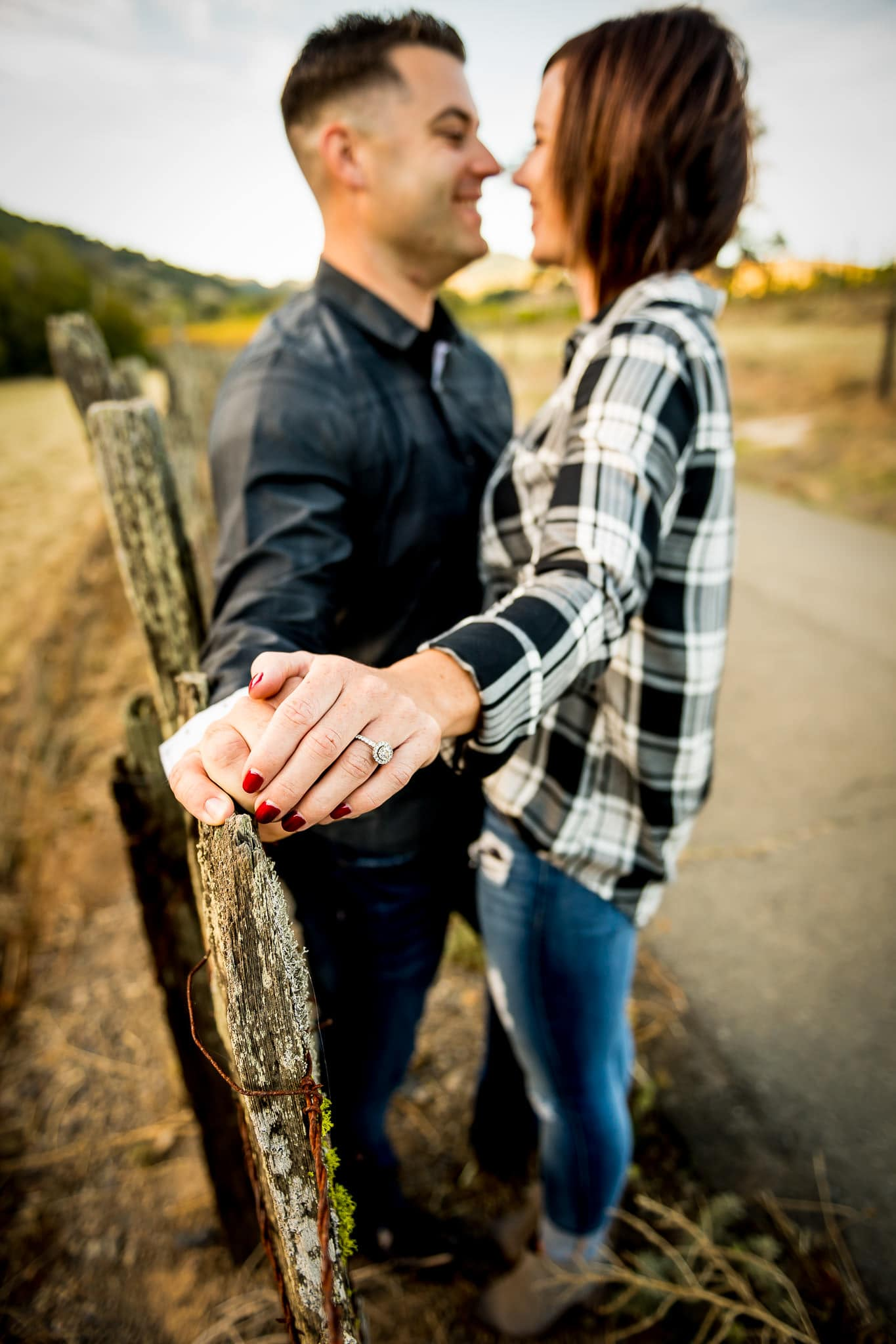Engagement ring focus photo of an engaged couple sharing a sweet moment along a fence running through Napa Valley