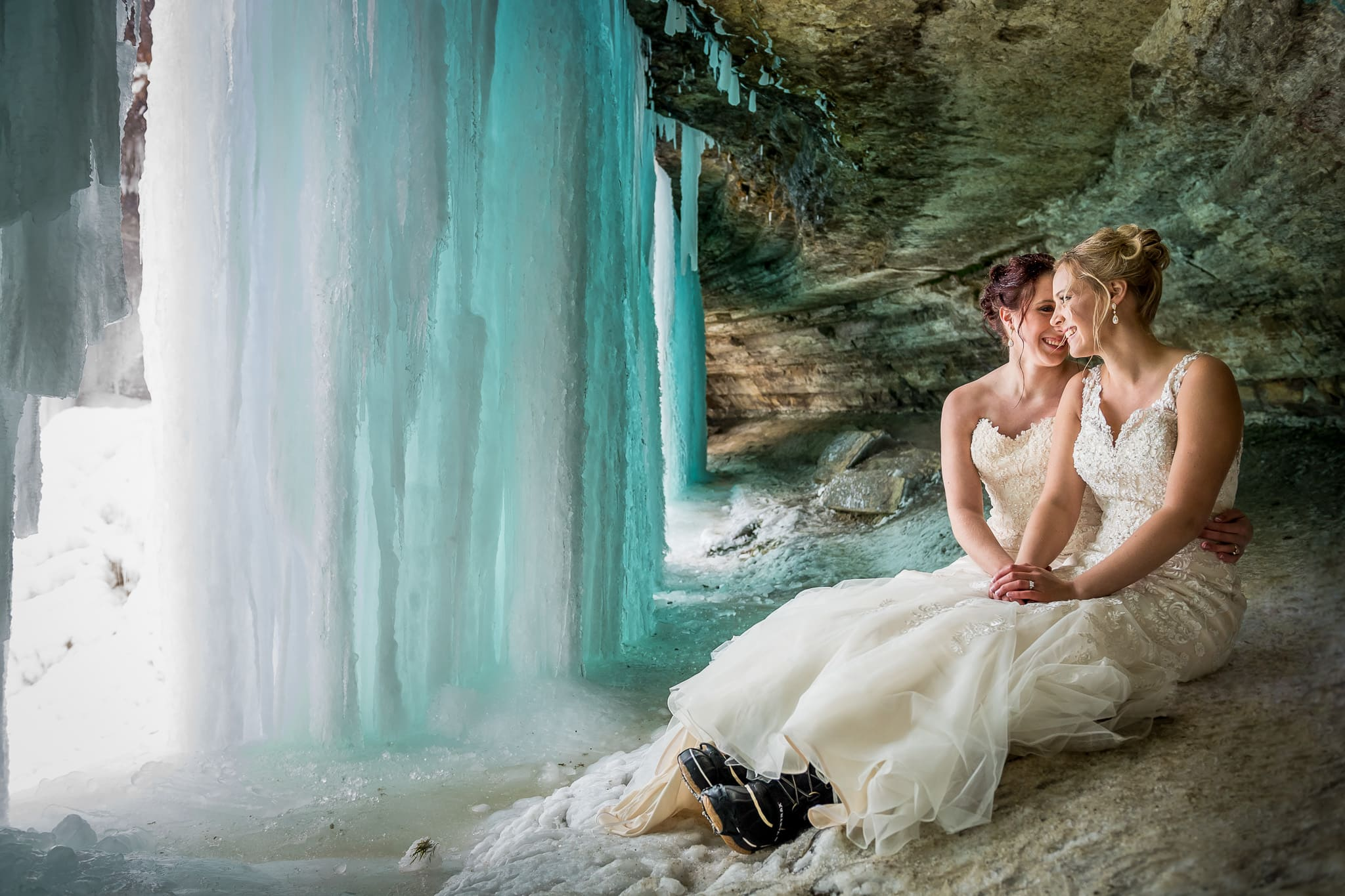 Two brides behind the frozen ice wall at Minnehaha Falls in Minneapolis