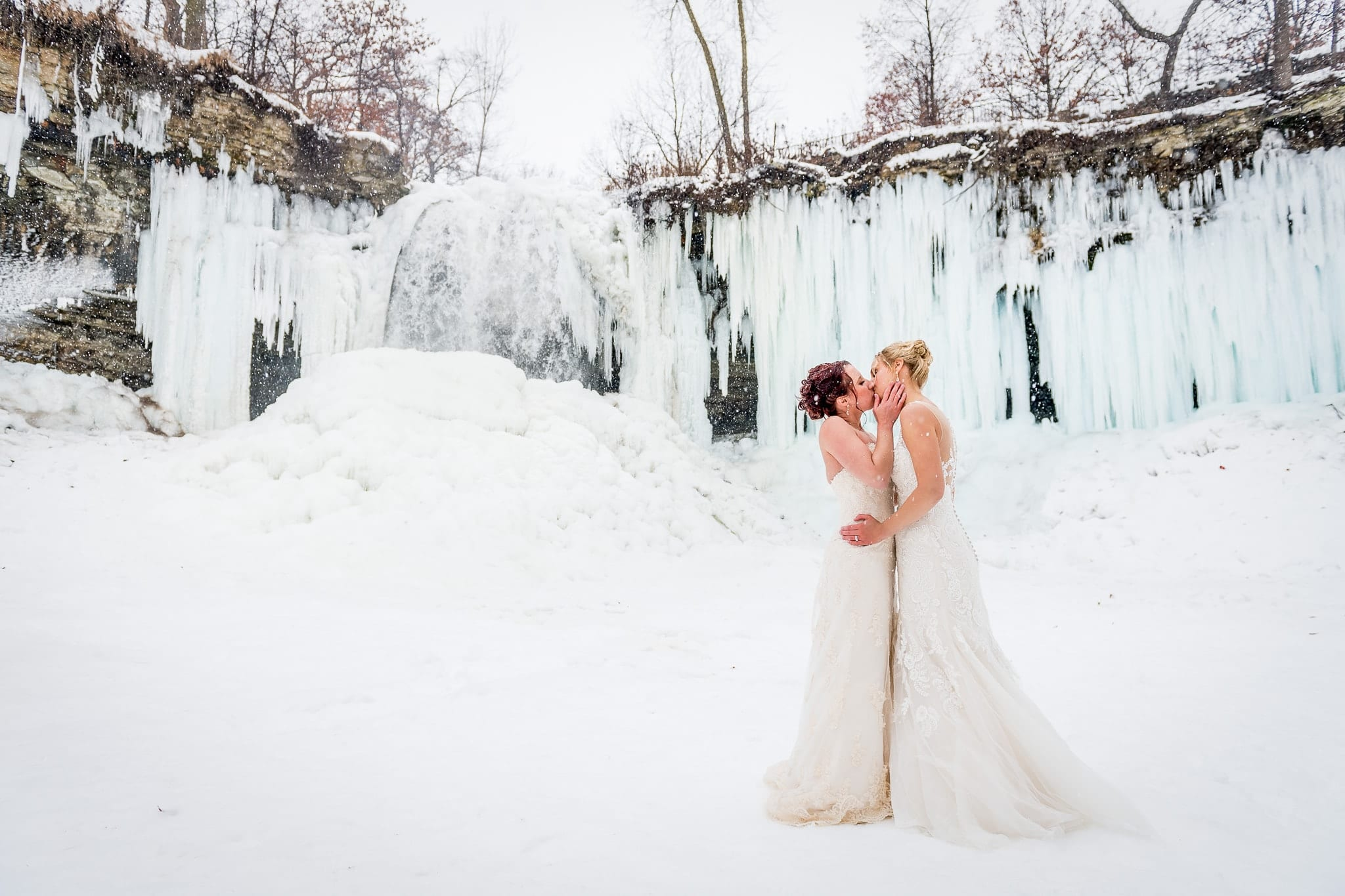 Two brides sharing a sweet kiss at Minnehaha Falls in Minneapolis on their wedding day