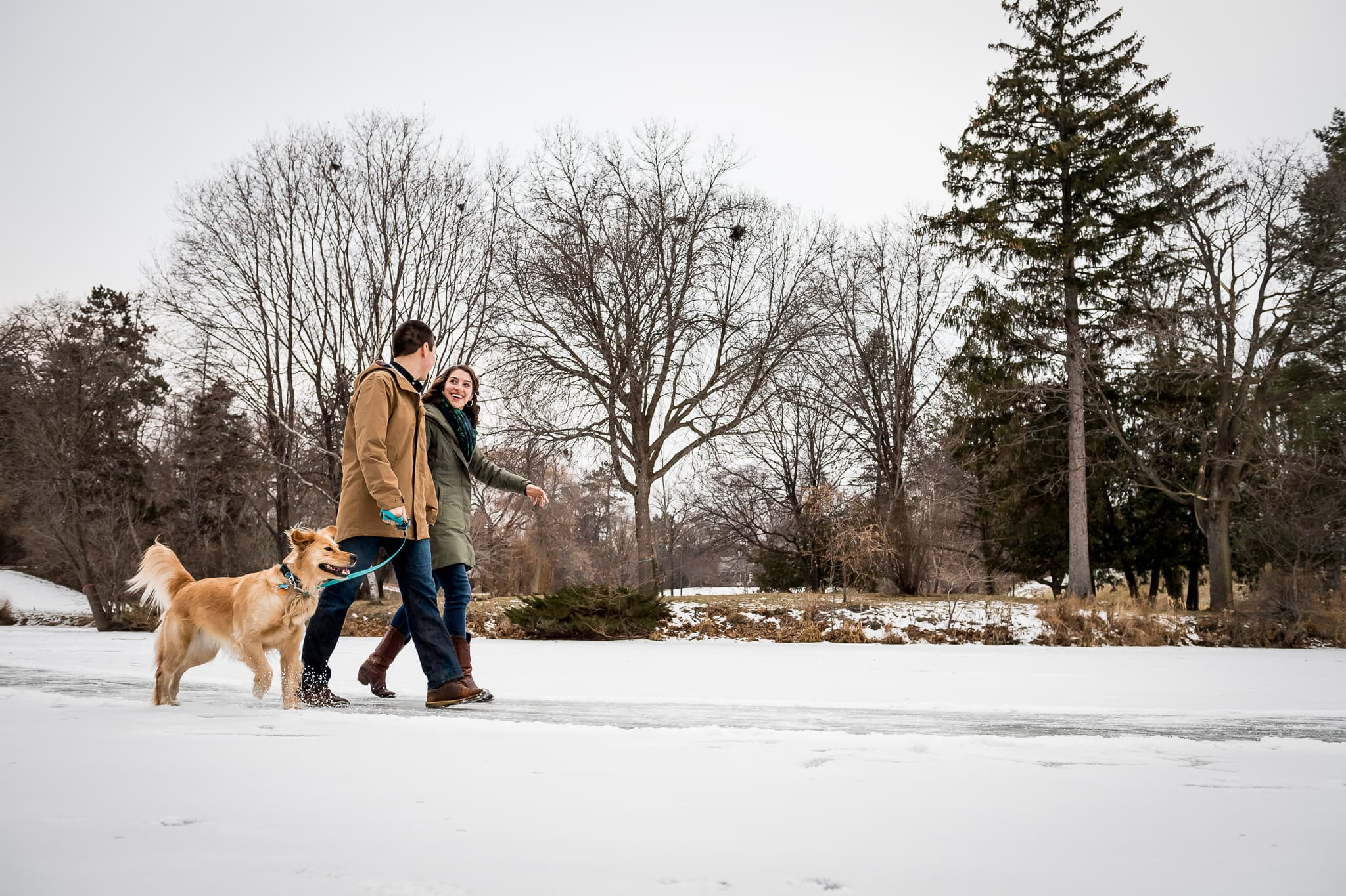 Couple walking with their dog on the frozen pond