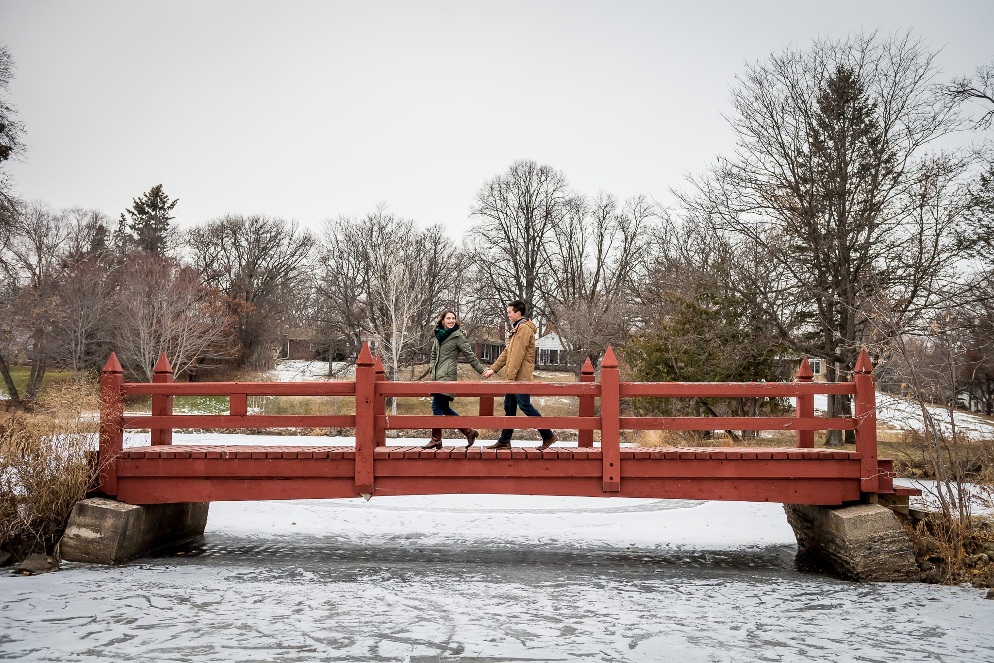 Wide view of couple walking in snowfall on the red wooden foot bridge