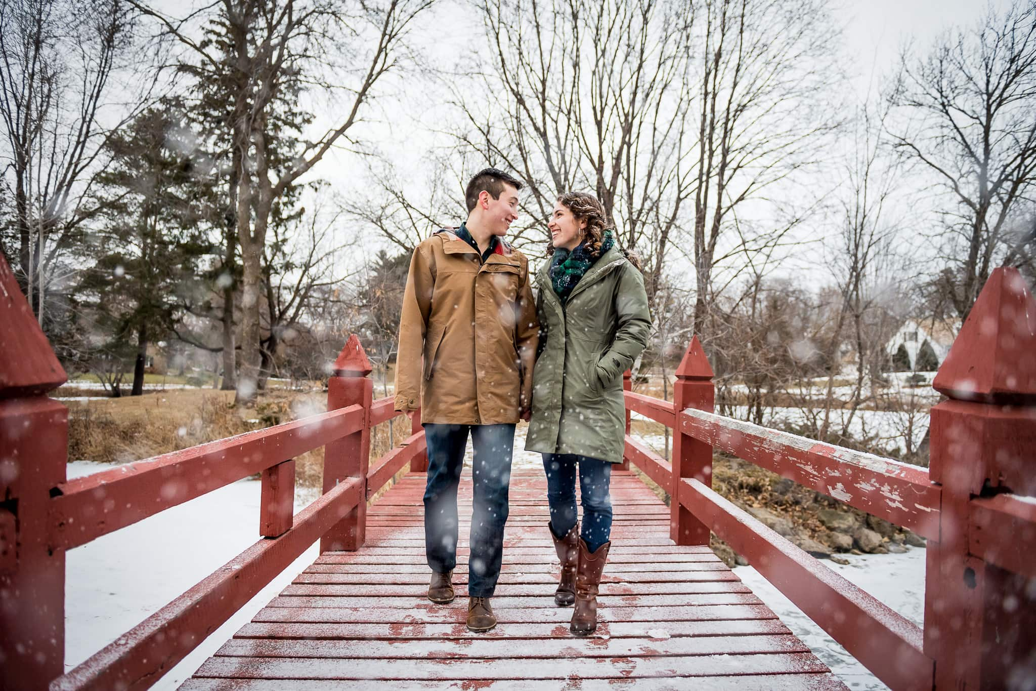 Knollwood neighborhood engagement photo of couple walking in snowfall on the red wooden foot bridge