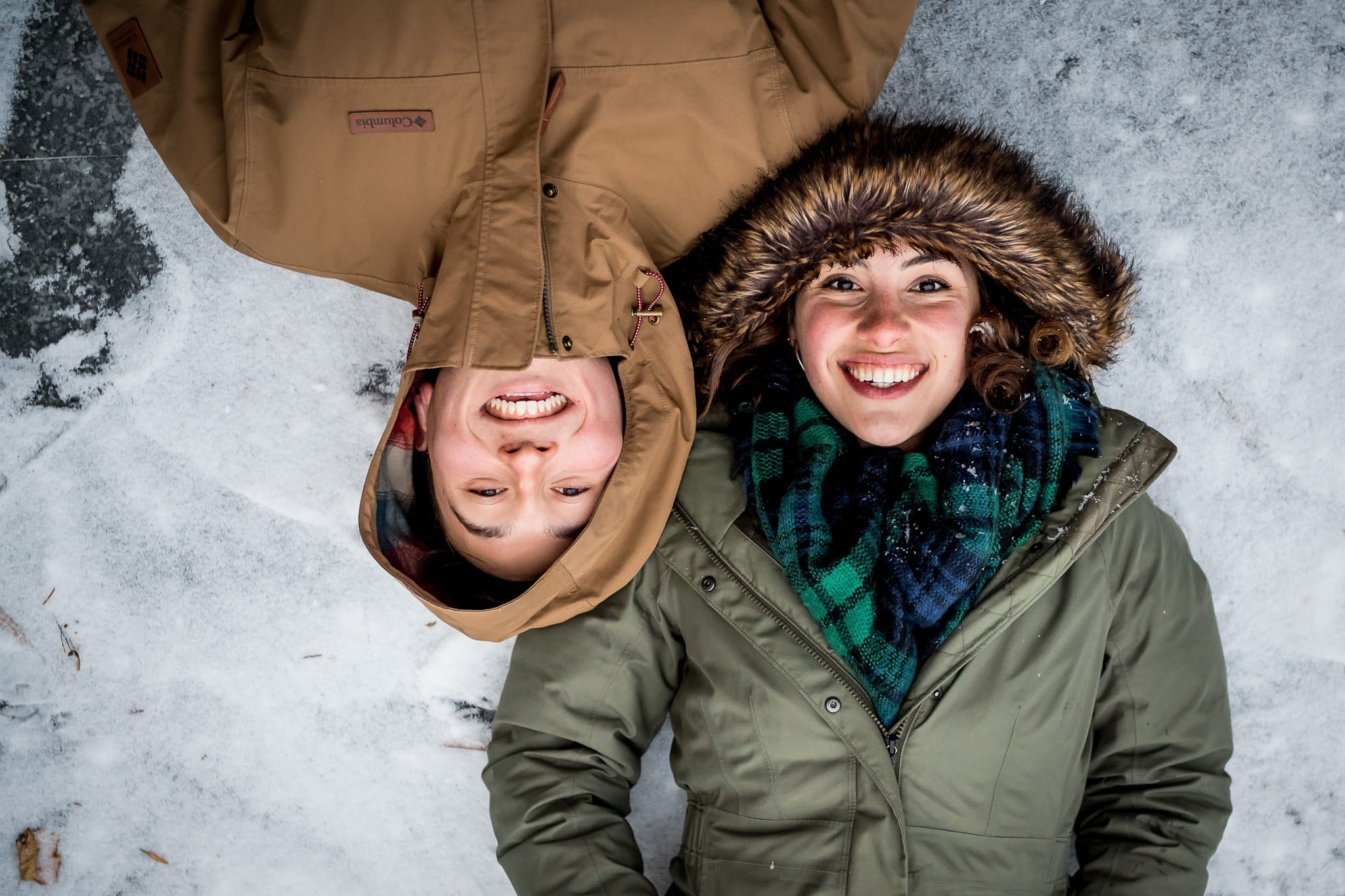close up of newly engaged couple laying together on the frozen pond