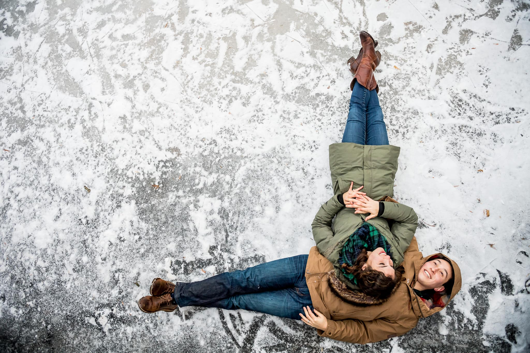 Newly engaged couple laying together on the frozen pond with the woman resting her head on her fiancées stomach with their bodies forming an L shape