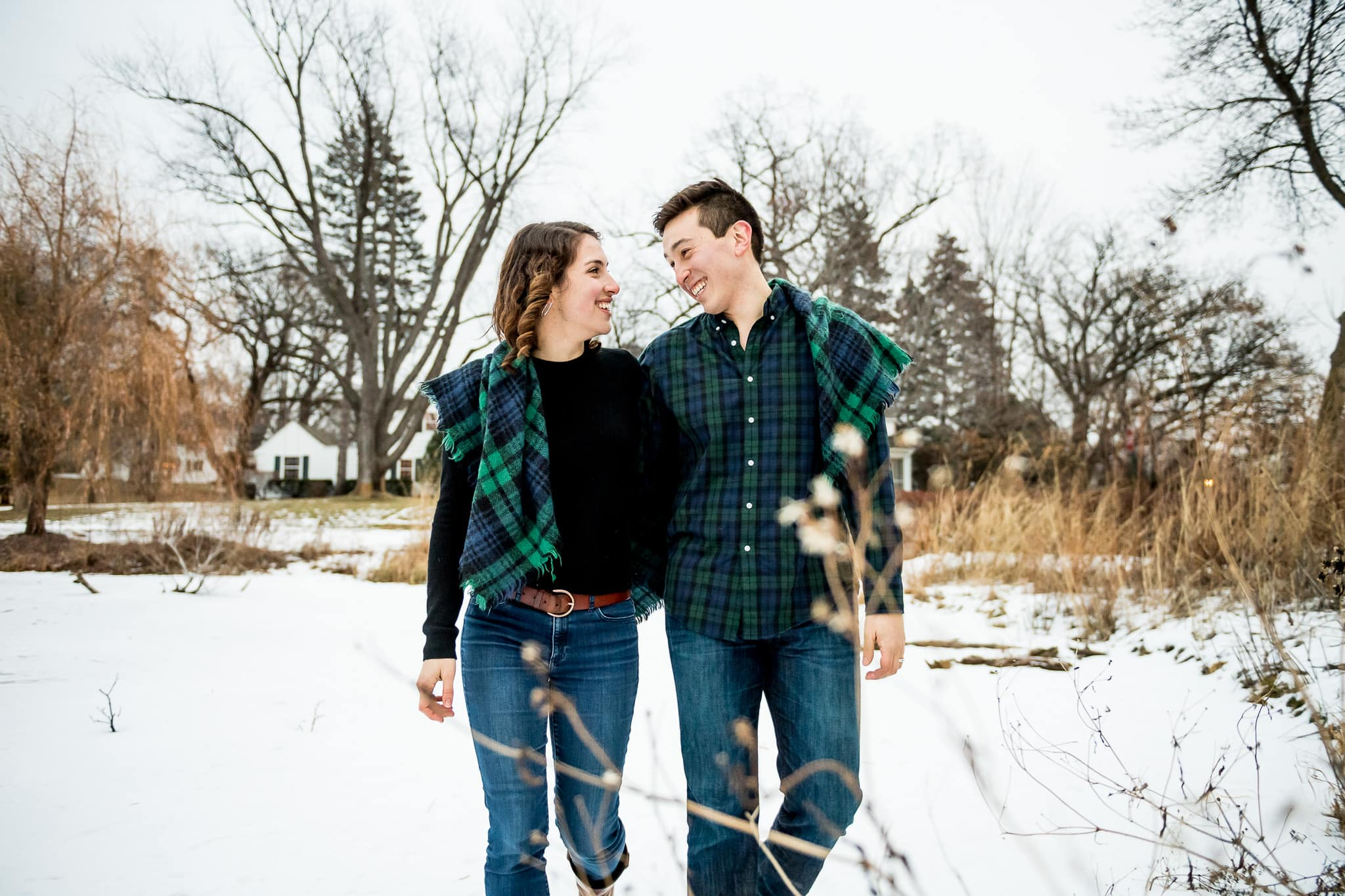 Couple walking on frozen pond with a blue and green plaid blanket wrapped around them as they smile at each other