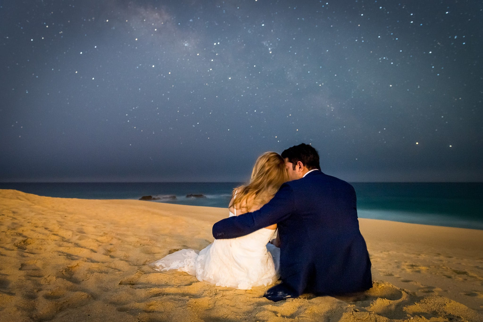 Newlywed bride and groom sitting on the sandy beach at night underneath a brilliant starry night sky at the end of their wedding day in Cabo San Lucas