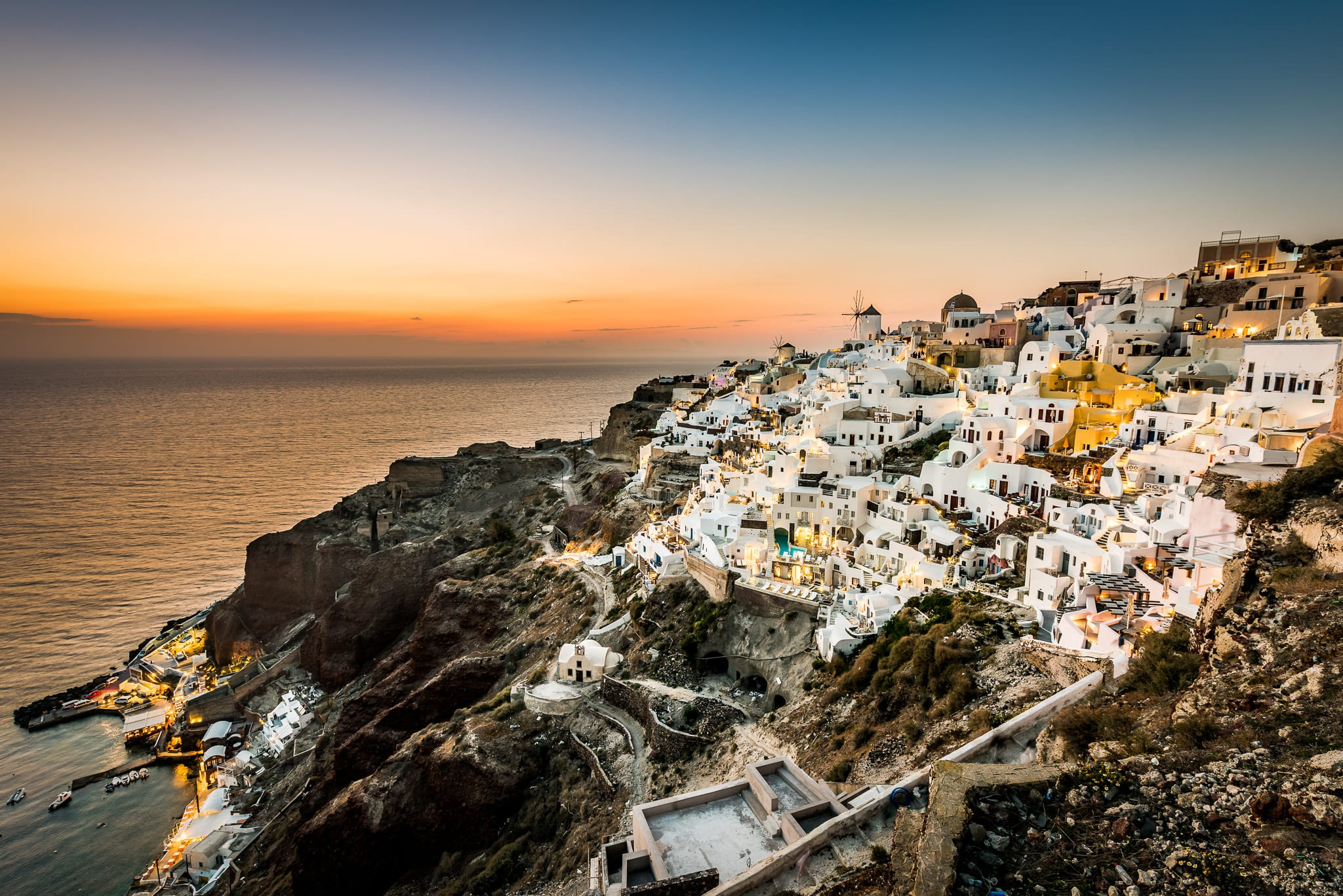 Beautiful sunset view from Oia Castle overlooking Amoudi Bay and the colorful village of Oia on the Greek island of Santorini