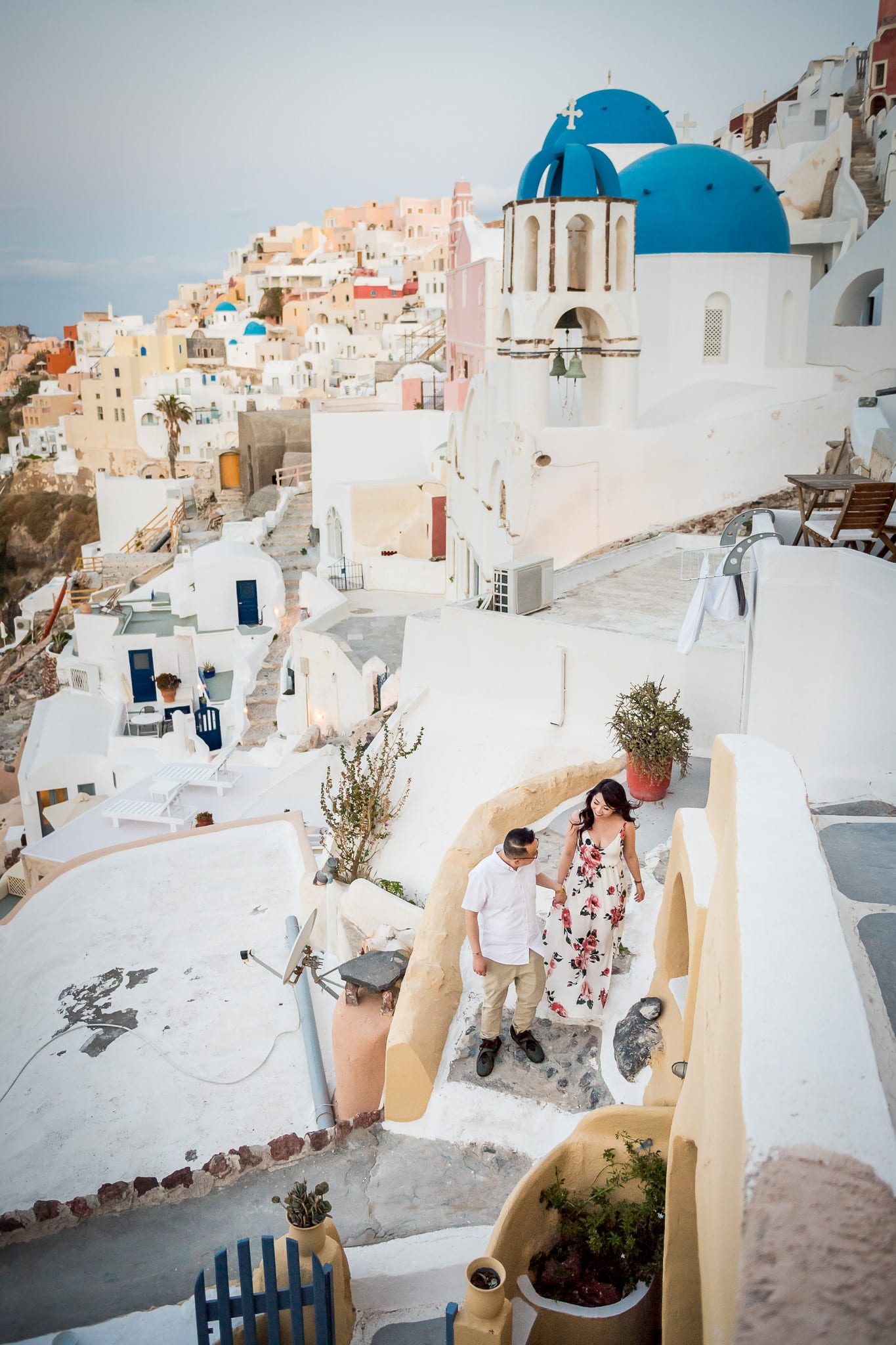Santorini Honeymoon photo session image of a couple walking down the stone stairs with the colorful Santorini island village of Oia in the background