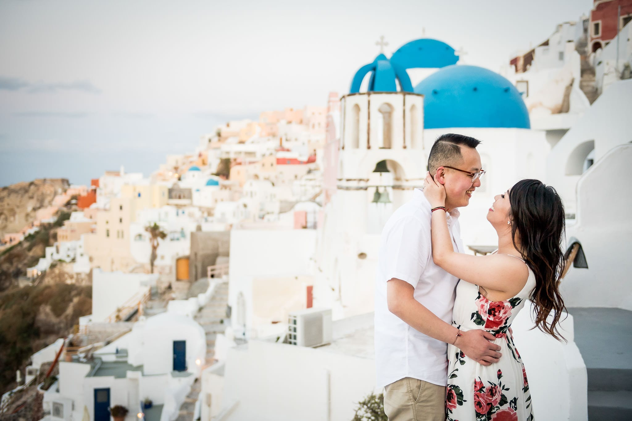 Santorini Honeymoon photo session image of a couple smiling at each other as they go in for a kiss, with the colorful Santorini island village of Oia in the background