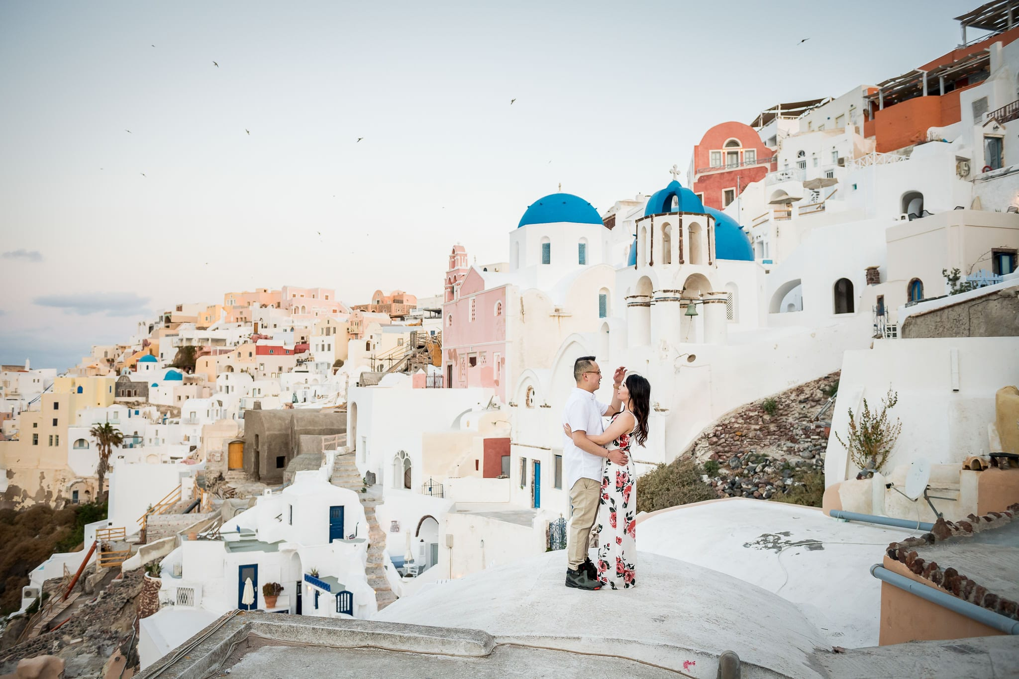 Santorini Honeymoon photo session wide-angle image of a newlywed man tenderly fixing the hair of his new bride with the colorful village of Oia in the background
