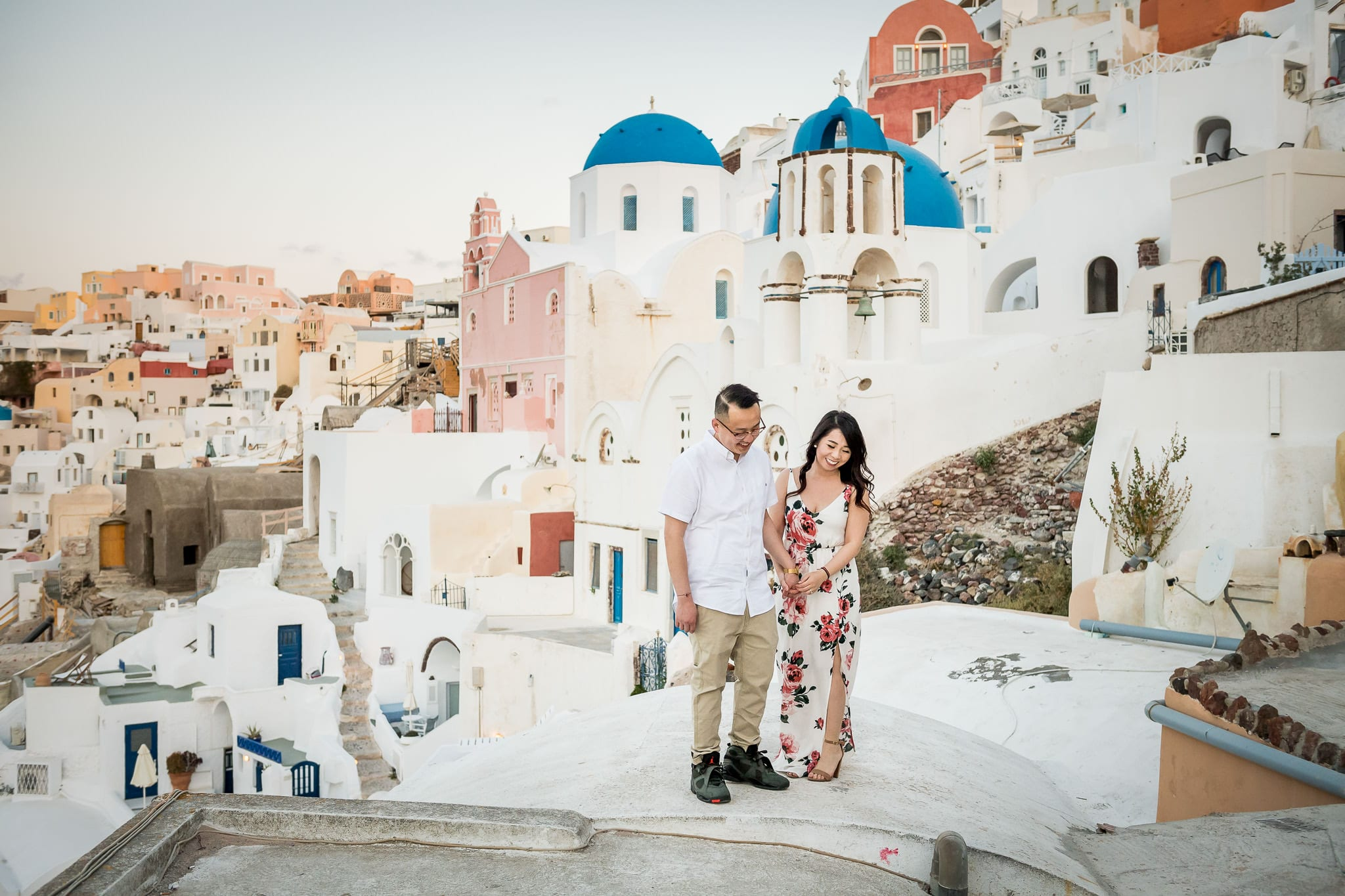 Santorini Honeymoon photo session wide-angle image of a couple holding hands with the colorful village of Oia in the background