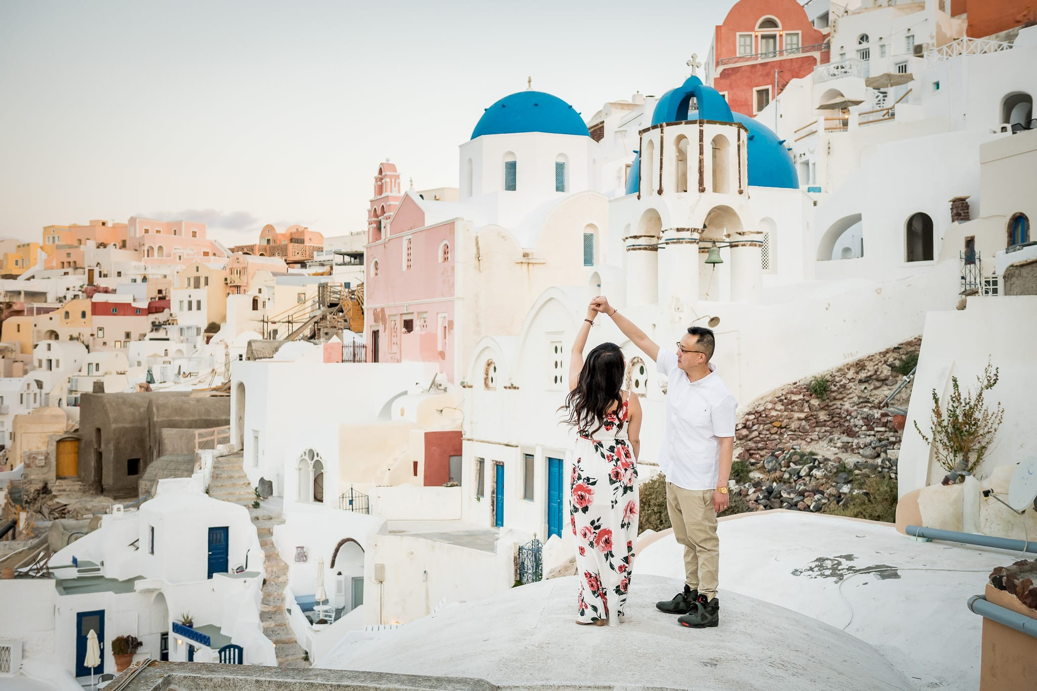 Santorini Honeymoon photo session image of a newlywed man twirling his new bride with the colorful village of Oia in the background